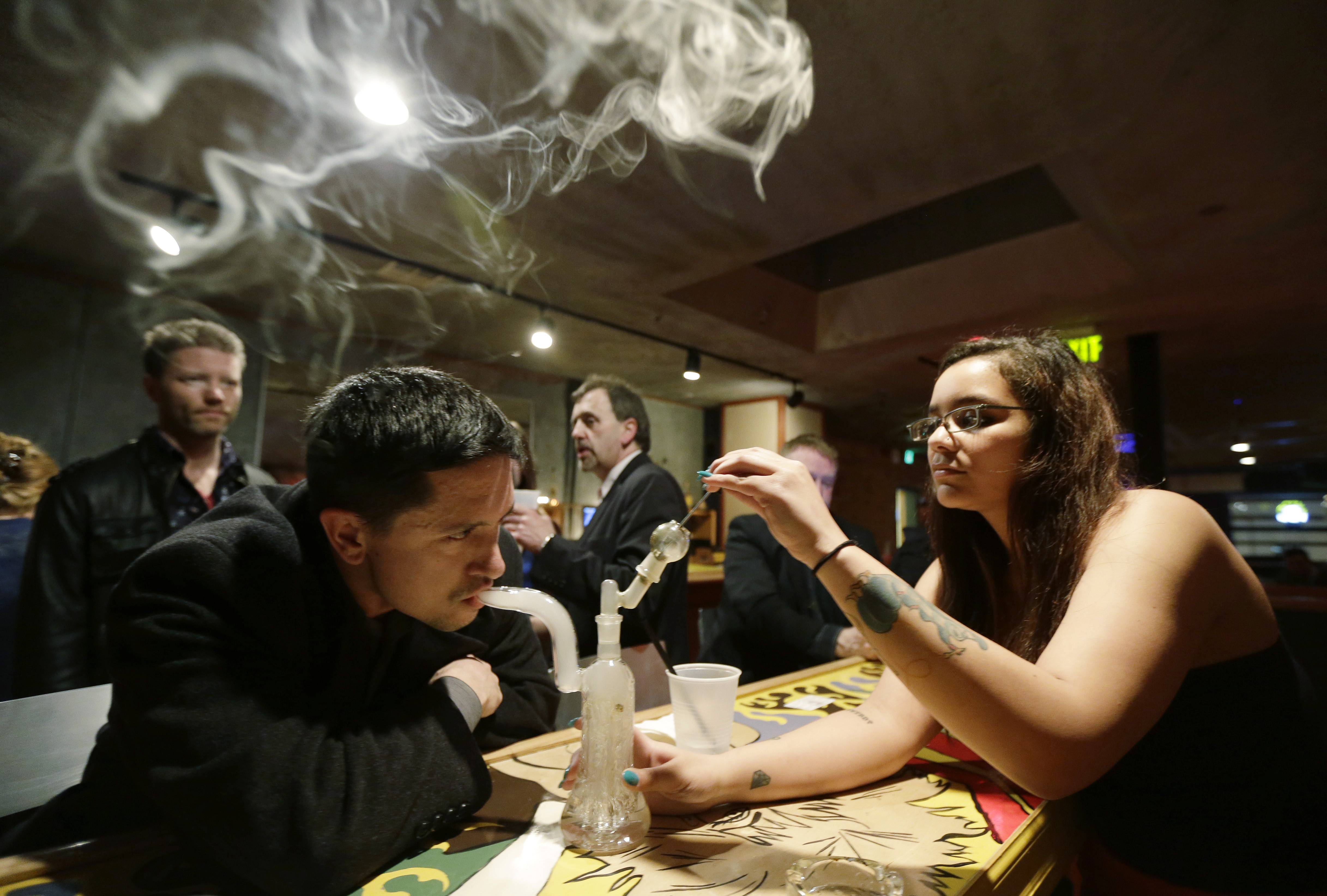 In this Saturday, March 2, 2013 file photo, John Connelly, left, inhales marijuana vapor just after midnight, with the help of bar worker Jenae DeCampo, right. Washington and Colorado became the first states to pass legislation legalizing marijuana use for adults over 21. Polls show that cigarette smoking is now less popular among teens than marijuana.