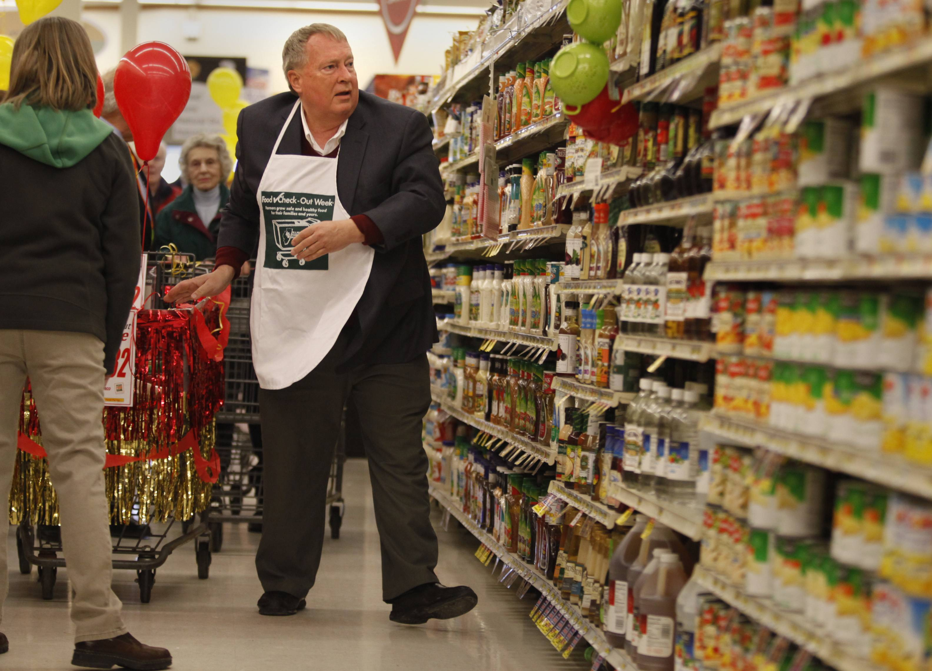 Batavia Mayor Jeff Schielke works quickly to grab as many nonperishable food items as he can Monday at the Jewel-Osco store in Batavia.