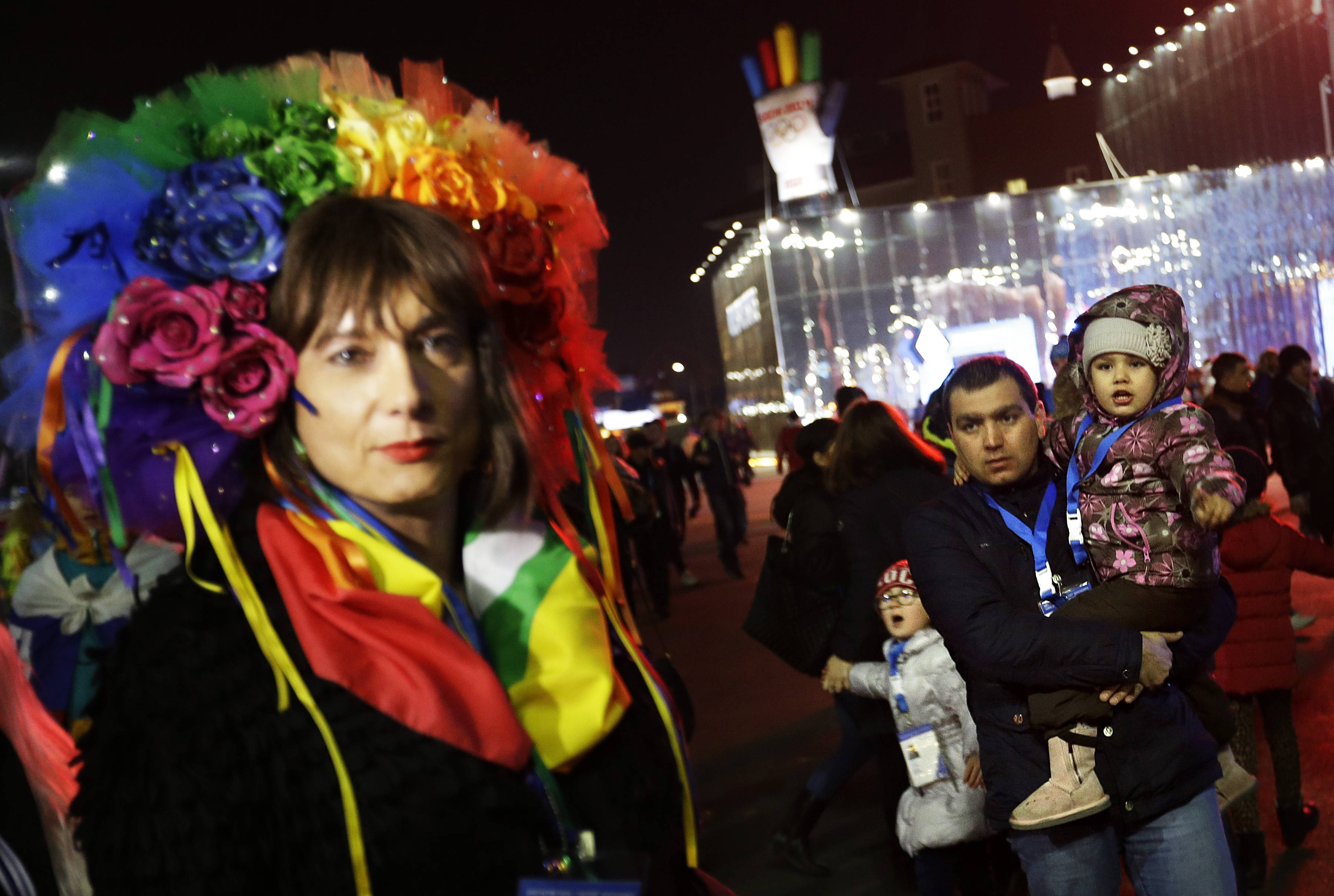 A father and children look on as Vladimir Luxuria, left, a former Communist lawmaker in the Italian parliament and prominent crusader for transgender rights, speaks out about gay rights while walking through the Olympic Plaza at the 2014 Winter Olympics, Monday, Feb. 17, 2014, in Sochi, Russia. Luxuria was soon after detained by police upon entering the Shayba Arena to attend a women's ice hockey match.