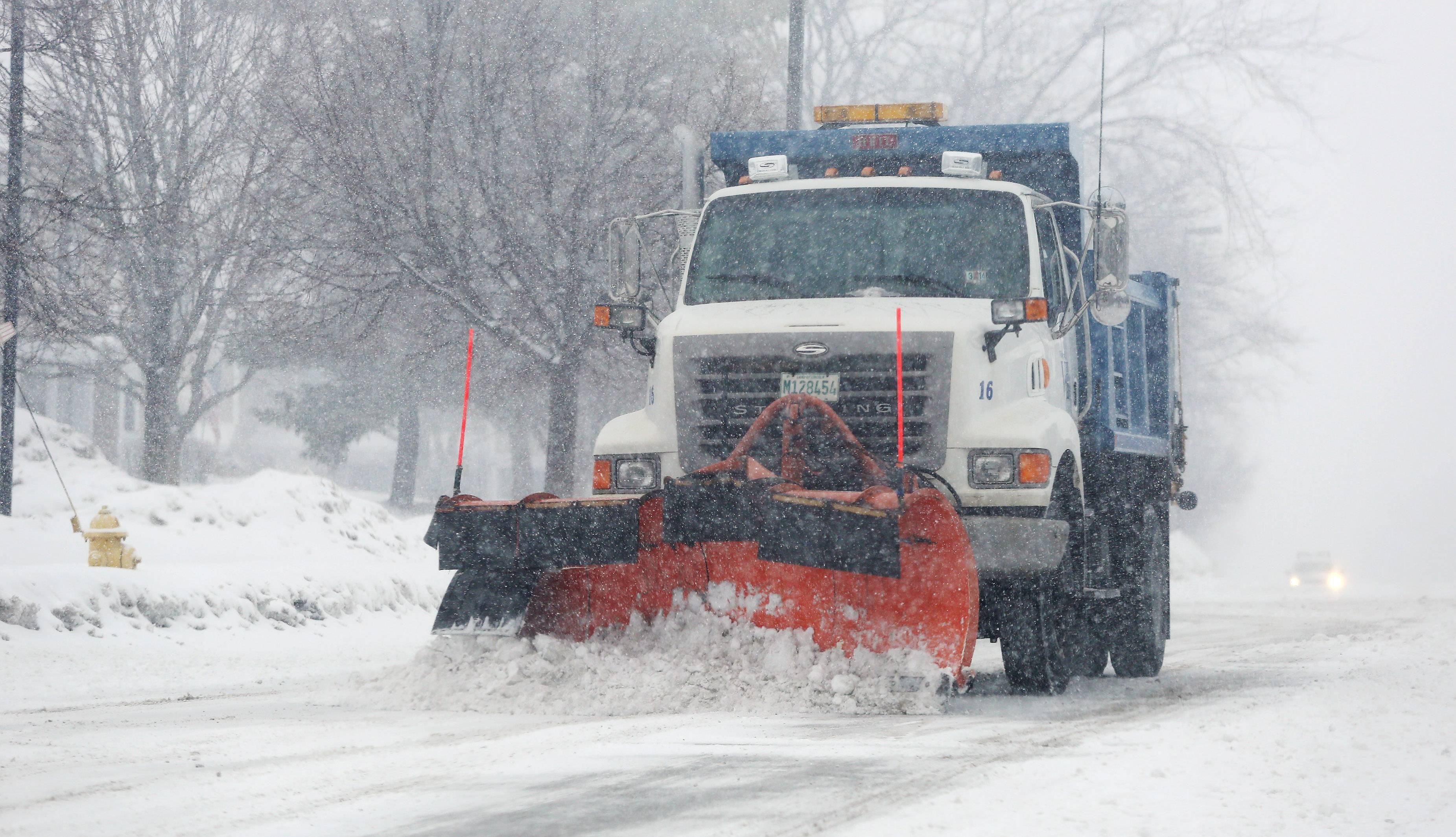 A Vernon Hills Public Works snowplow clears Deerpath Road before rush hour traffic Monday. Snow fell throughout the day in Lake County.