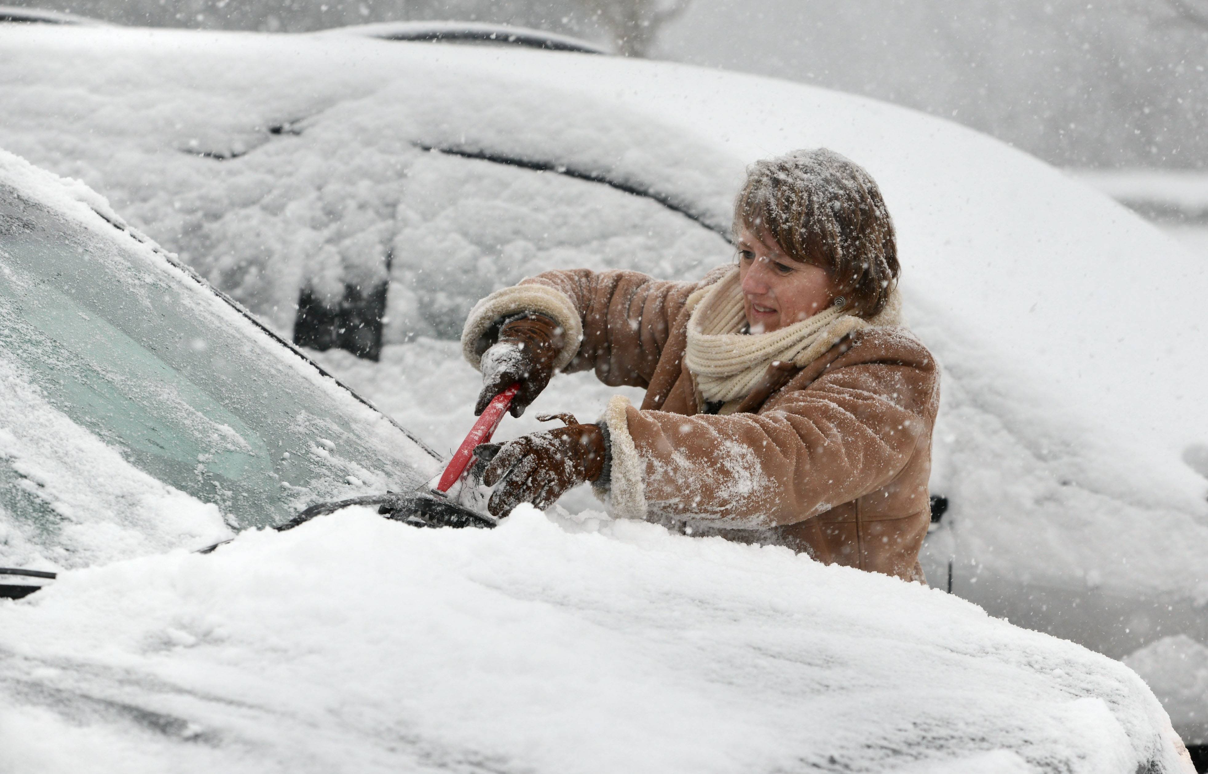 Sara Jensen of Mundelein cleans off her car after leaving work Monday afternoon from the Centre Club in Libertyville.