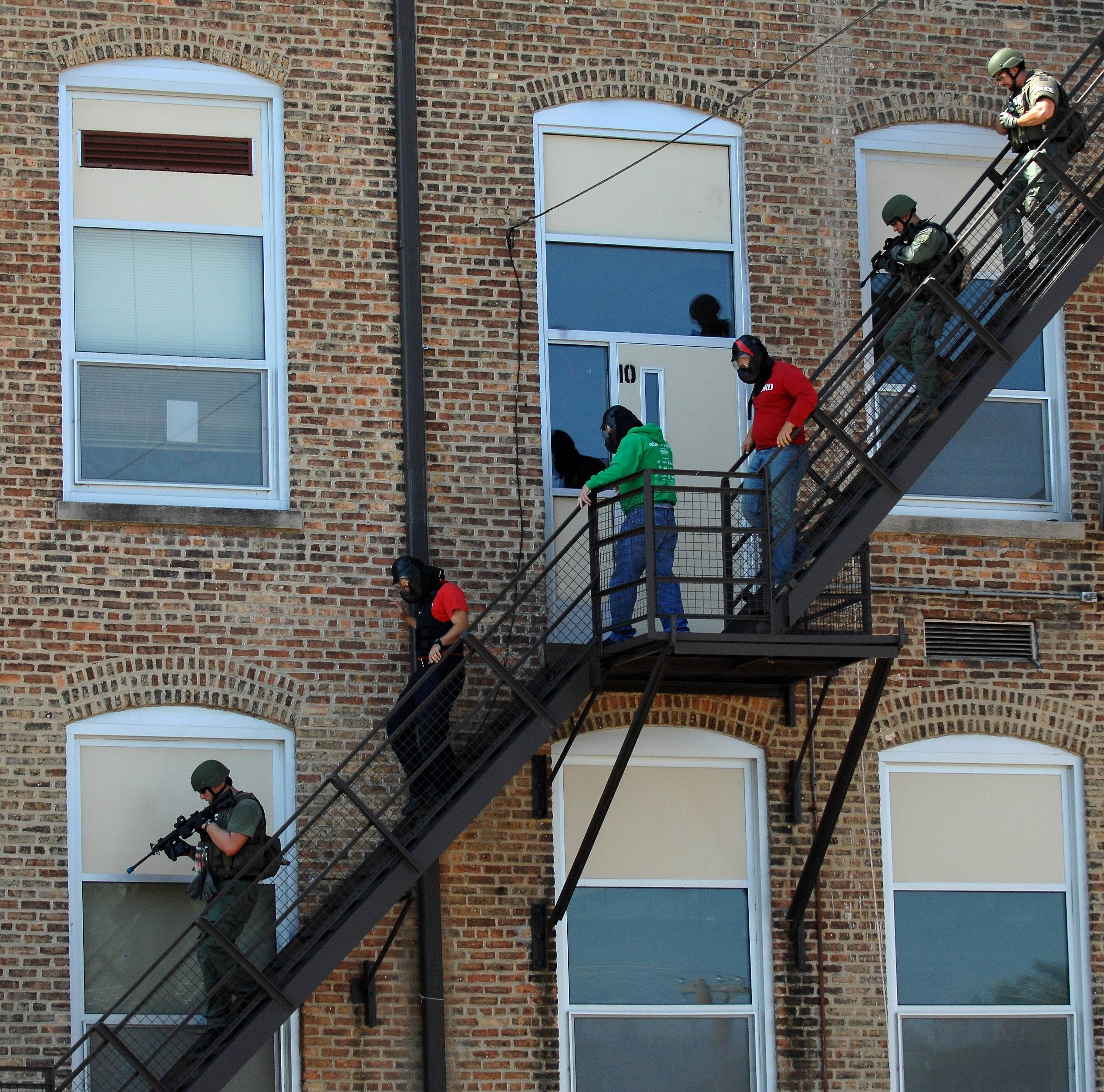 "A SWAT team leads shooting ""suspects"" down a fire escape during a summer training exercise at Gifford Street High School in Elgin. Students were not involved in the drill."