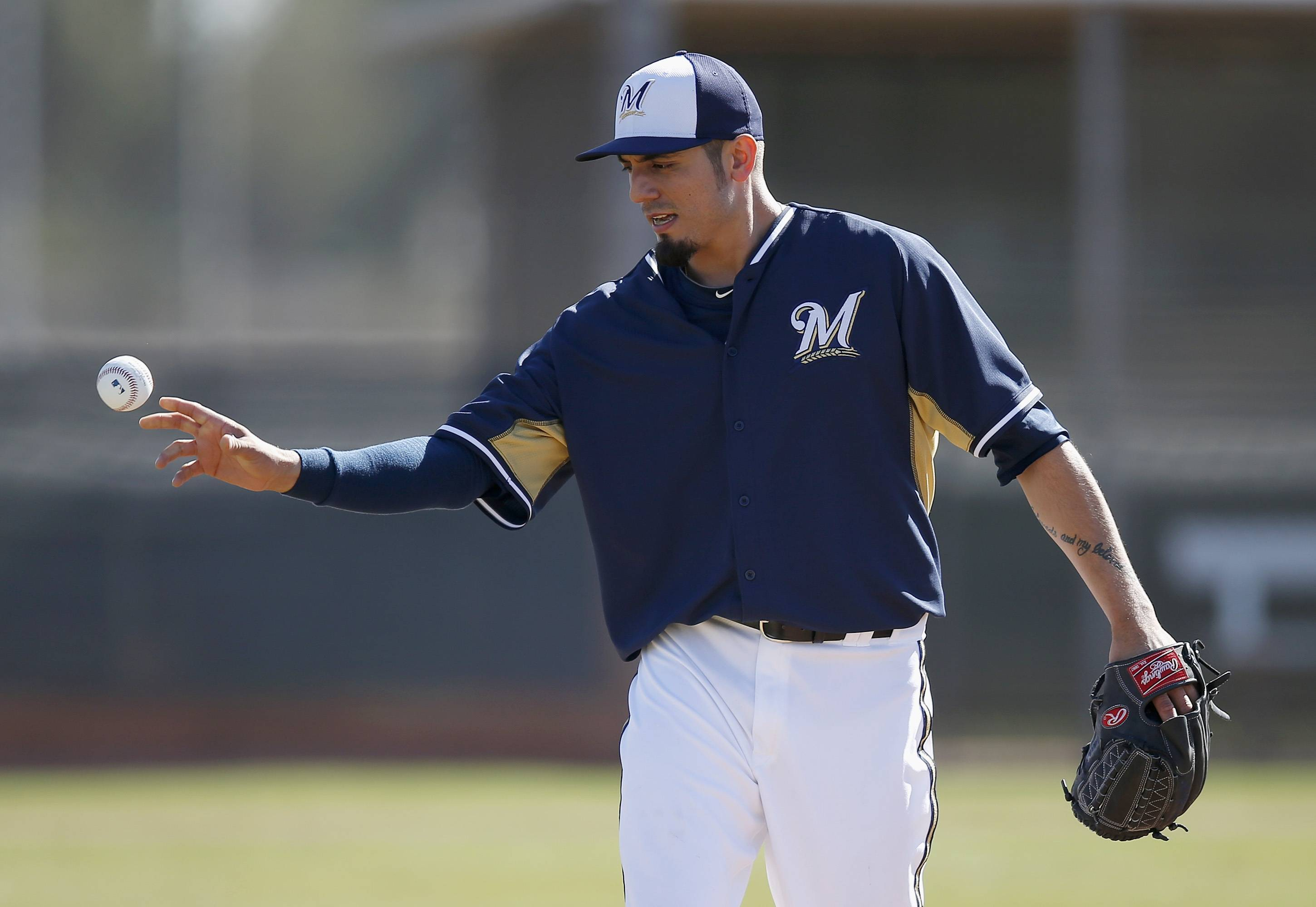 The Brewers' Matt Garza flips a baseball into a bucket after covering first base on an infield grounder during spring training practice Monday in Phoenix.