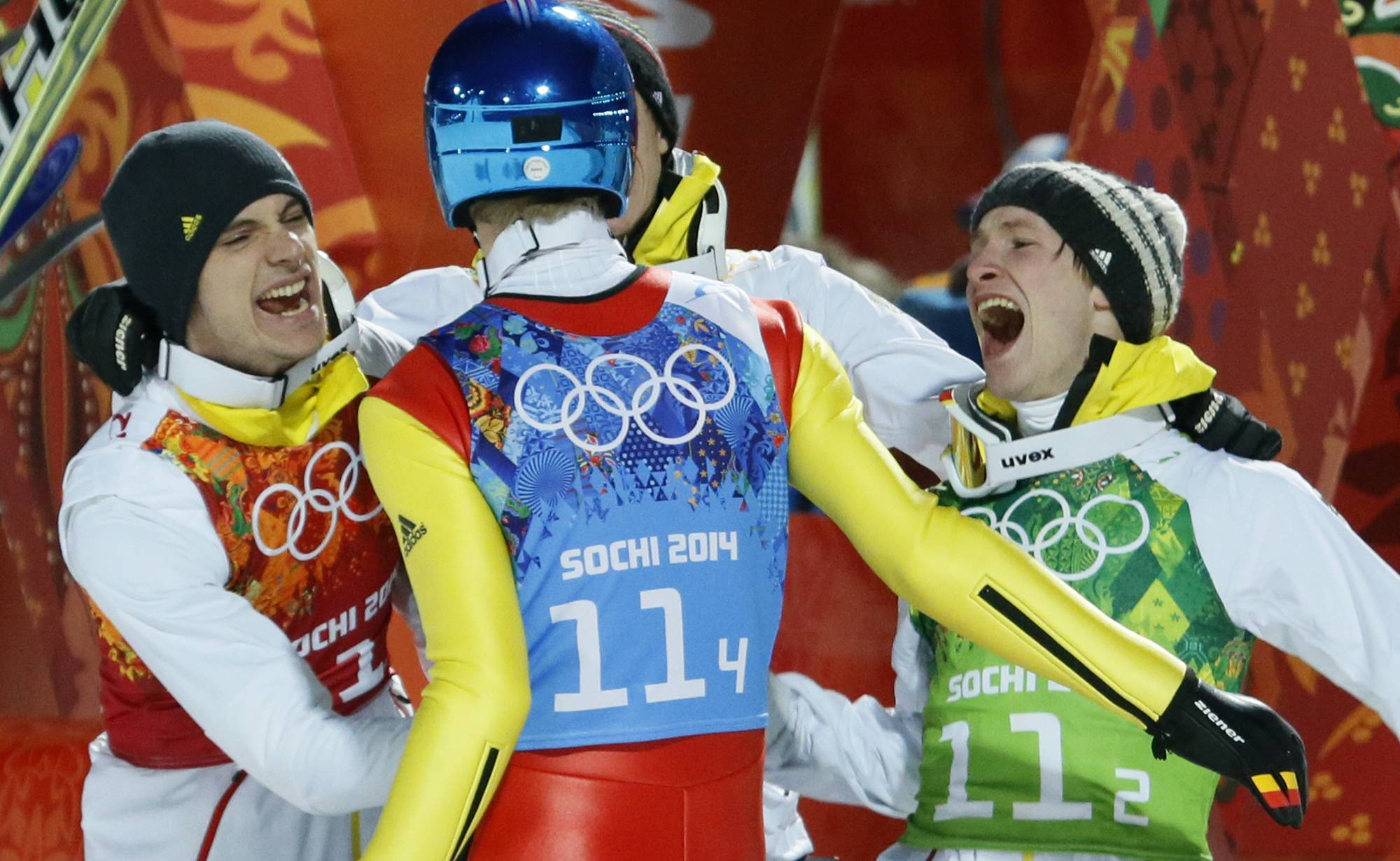 Germany's Andreas Wank, left, and Marinus Kraus, right, congratulate teammate Severin Freund after learning they won the gold during the ski jumping team competition Monday at the Sochi Olympics.