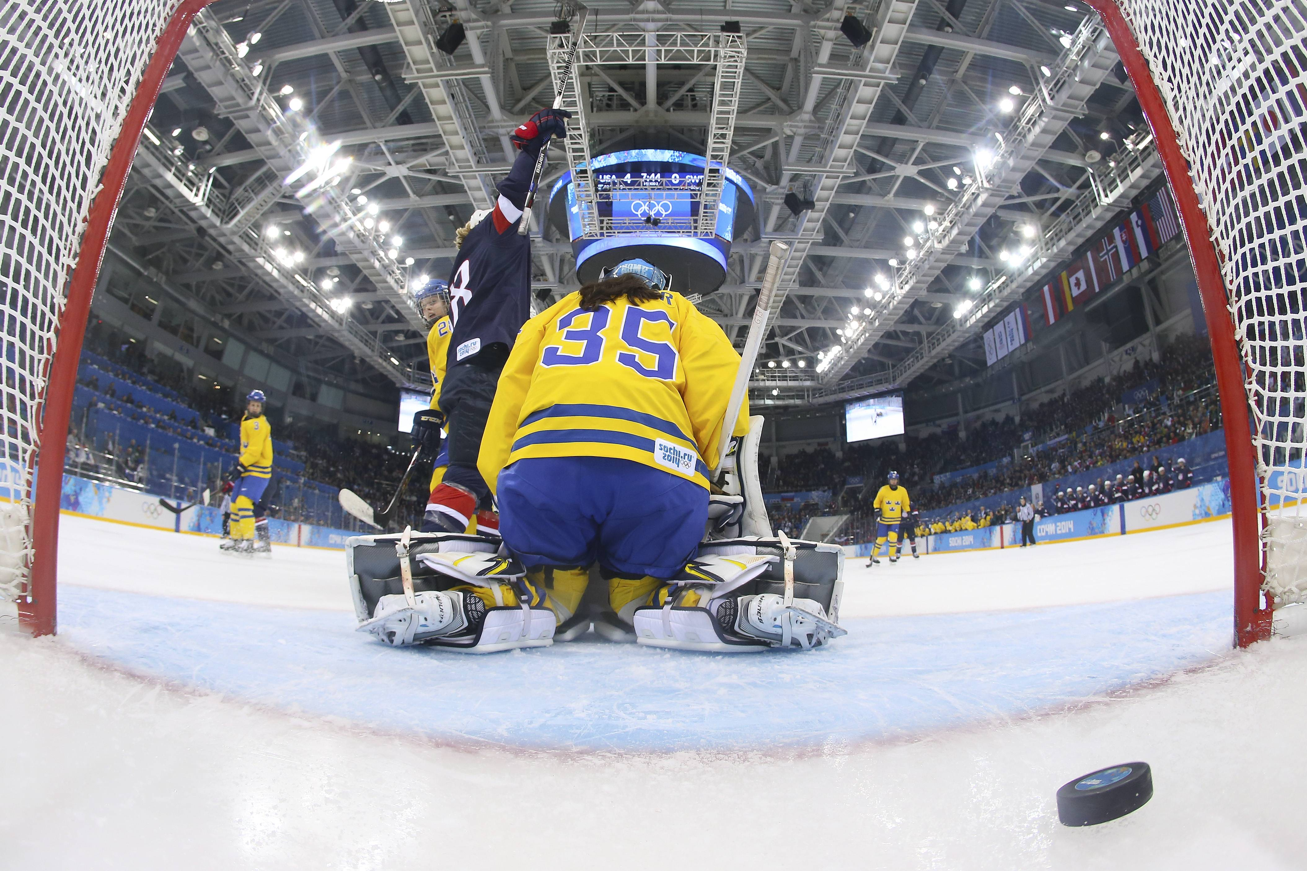 Lyndsey Fry celebrates Megan Bozek's goal as Goalkeeper Valentina Wallner of Sweden sits on her knees Monday during the second period of the 2014 Winter Olympics women's semifinal ice hockey game at Shayba Arena in Sochi, Russia.
