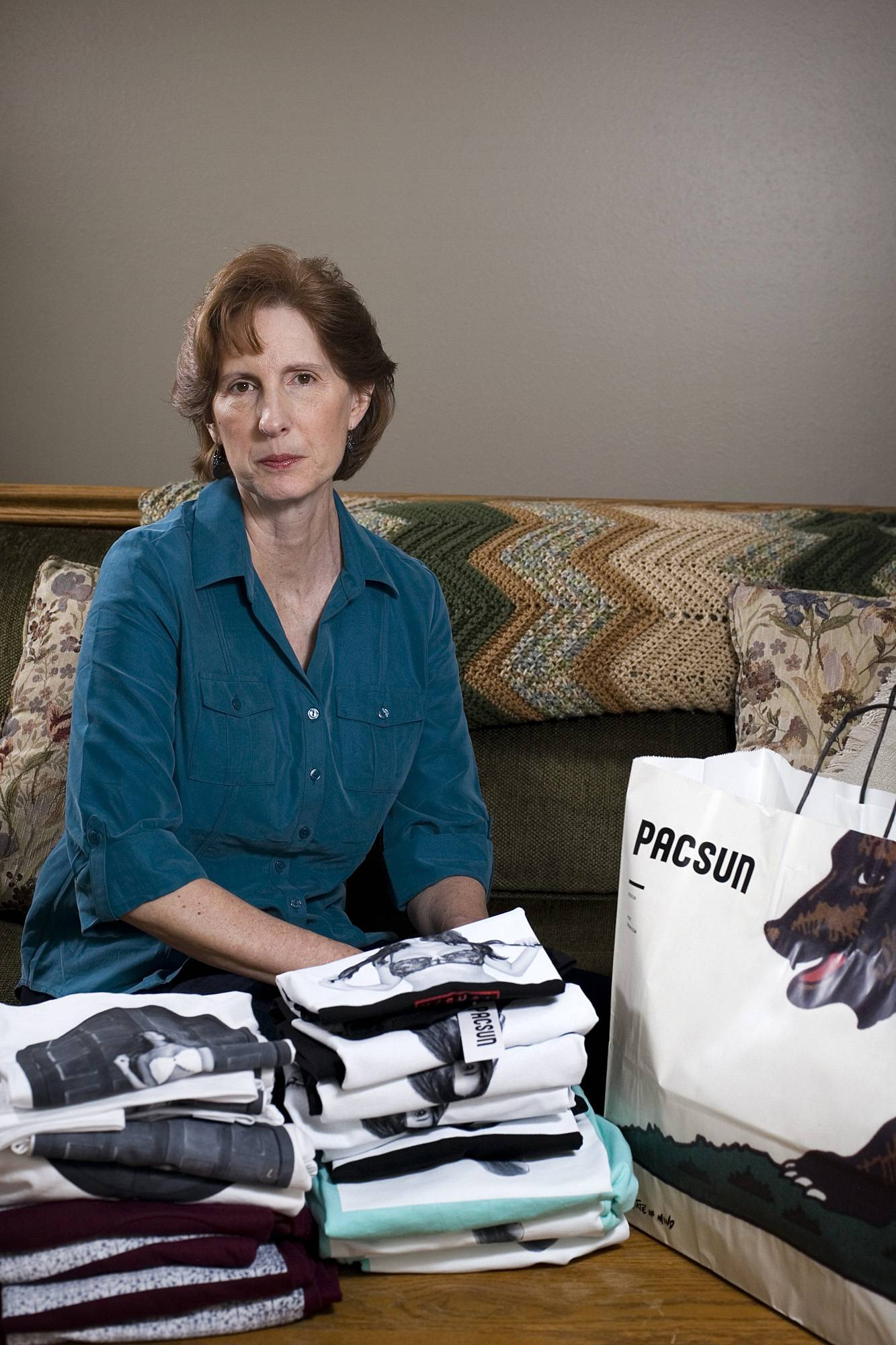 Judy Cox sits Monday next to a stack of T-shirts with what she believes are pornographic designs.
