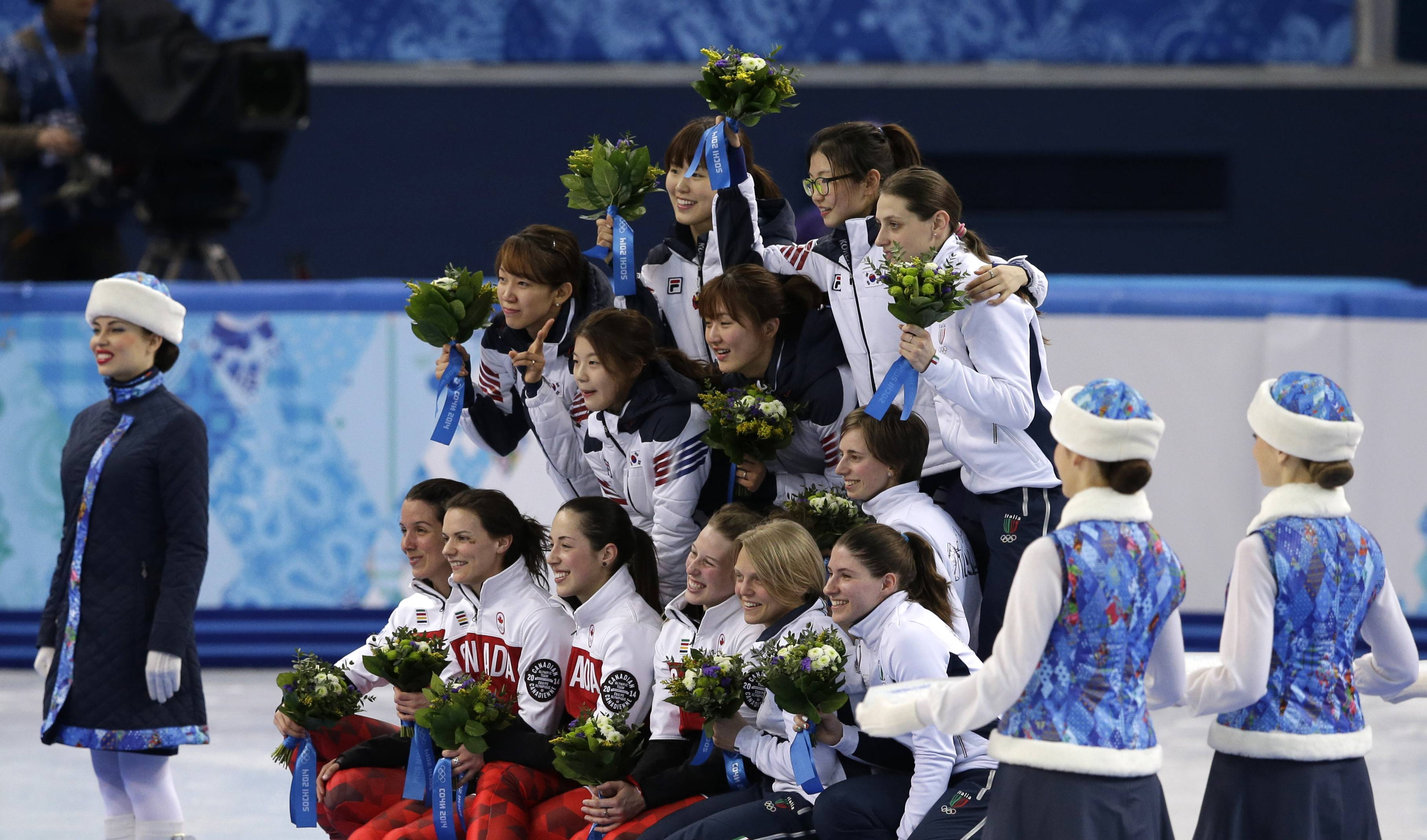 The South Korean team, top left, the Canadian team, front left, and the Italian team, top and bottom right, celebrate Tuesday during the flower ceremony for the women's 3000m short track speedskating relay final at the Iceberg Skating Palace during the 2014 Winter Olympics in Sochi, Russia. South Korea placed first, followed by Canada and Italy.