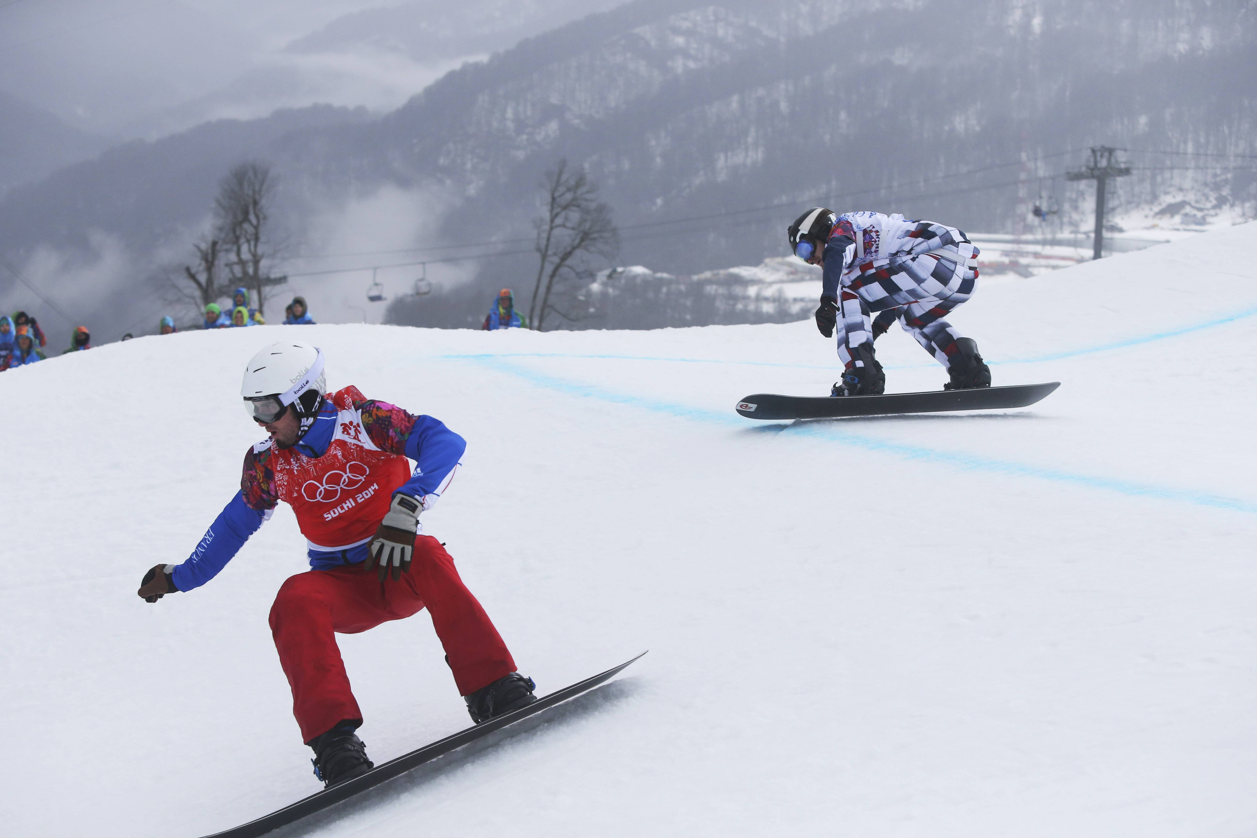 Gold medalist Pierre Vaultier of France leads silver medalist Nikolai Olyunin of Russia in the men's snowboard cross final at the Rosa Khutor Extreme Park Tuesday during the 2014 Winter Olympics in Krasnaya Polyana, Russia.