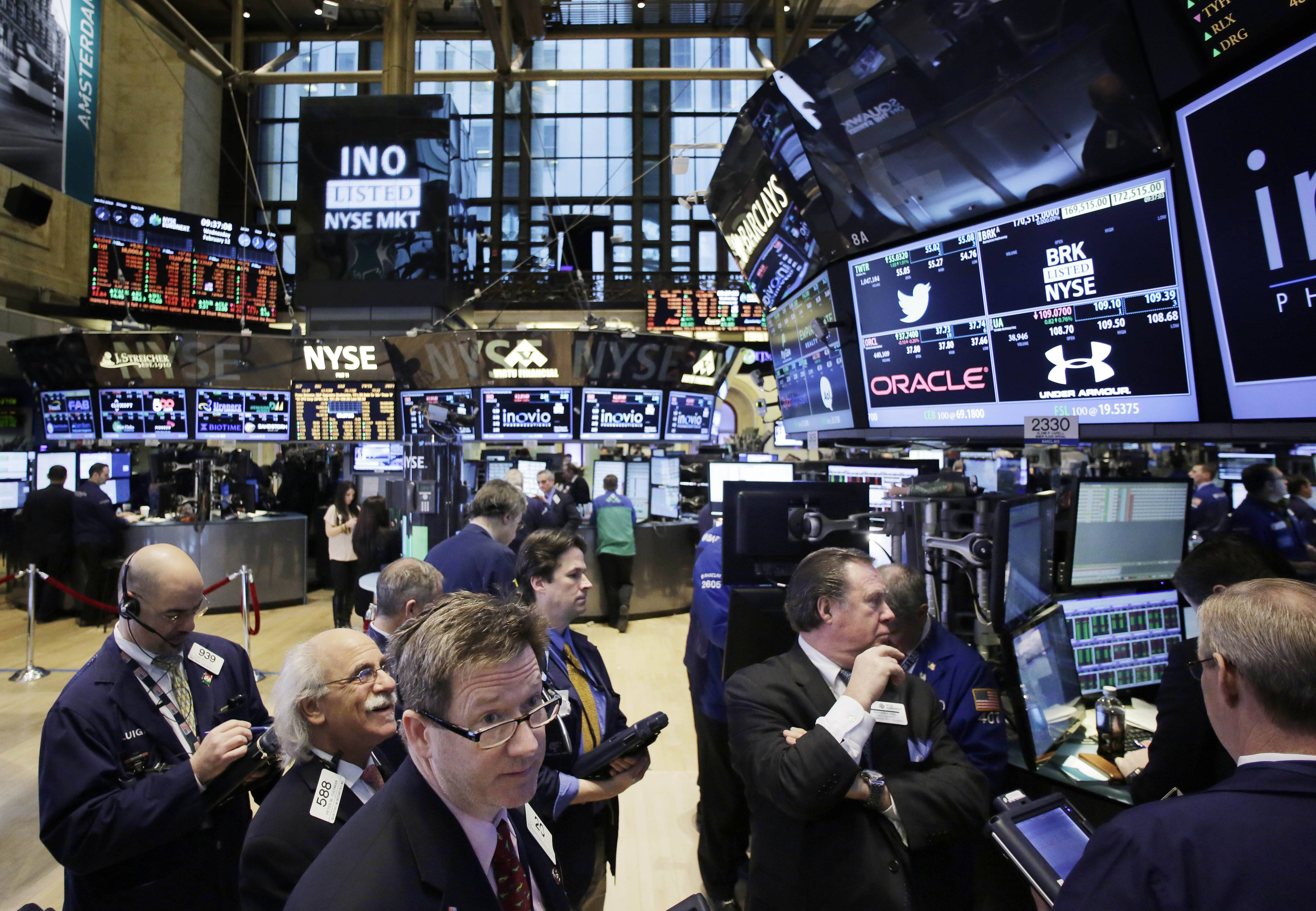 Traders monitor stock prices last week at the New York Stock Exchange. Stocks were mostly higher in midday trading Tuesday as investors returned from a long holiday weekend.