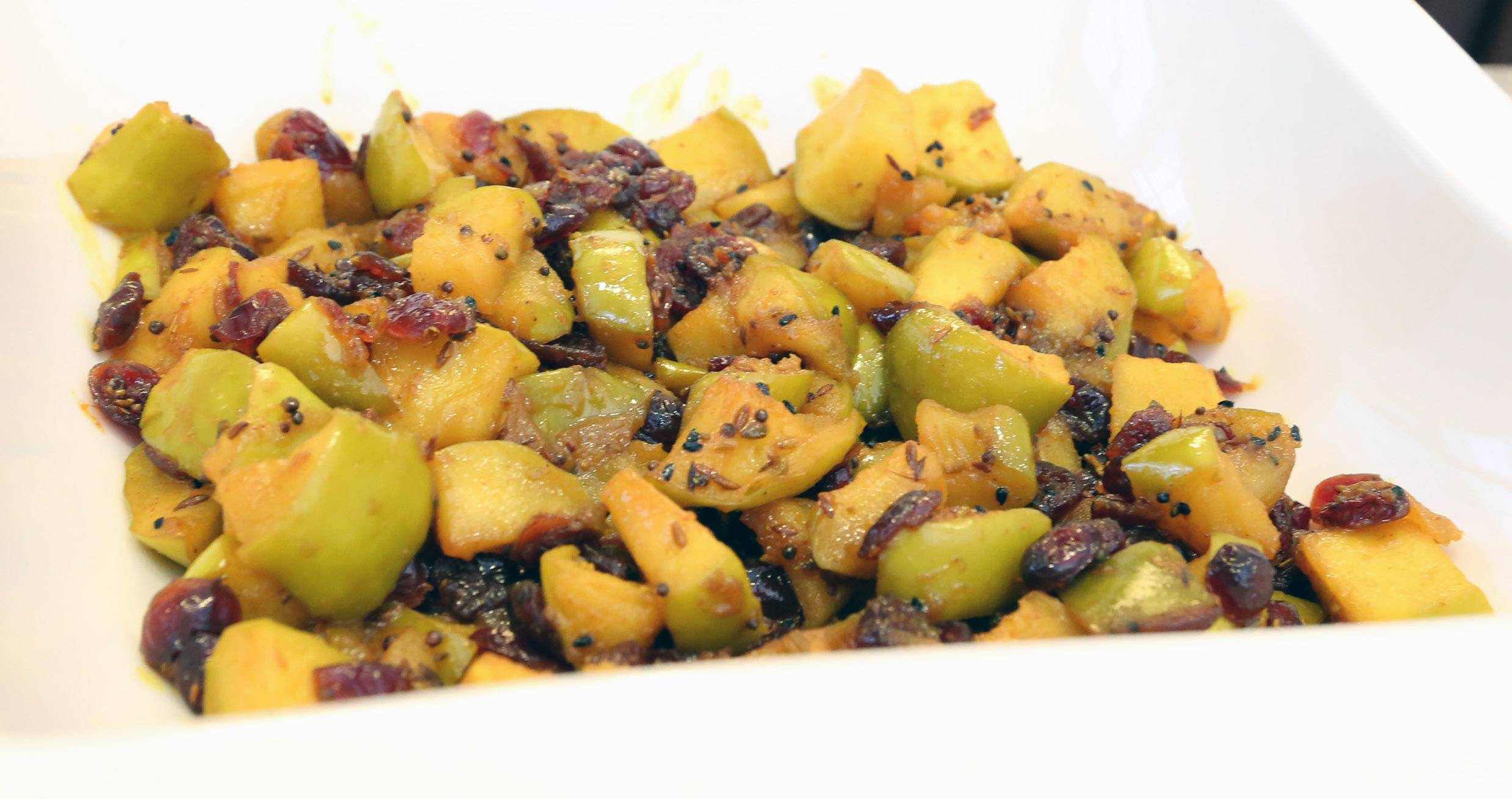 Apples and cranberries simmer with fennel, turmeric and other spices in Sushma Bhanot's sabzi.