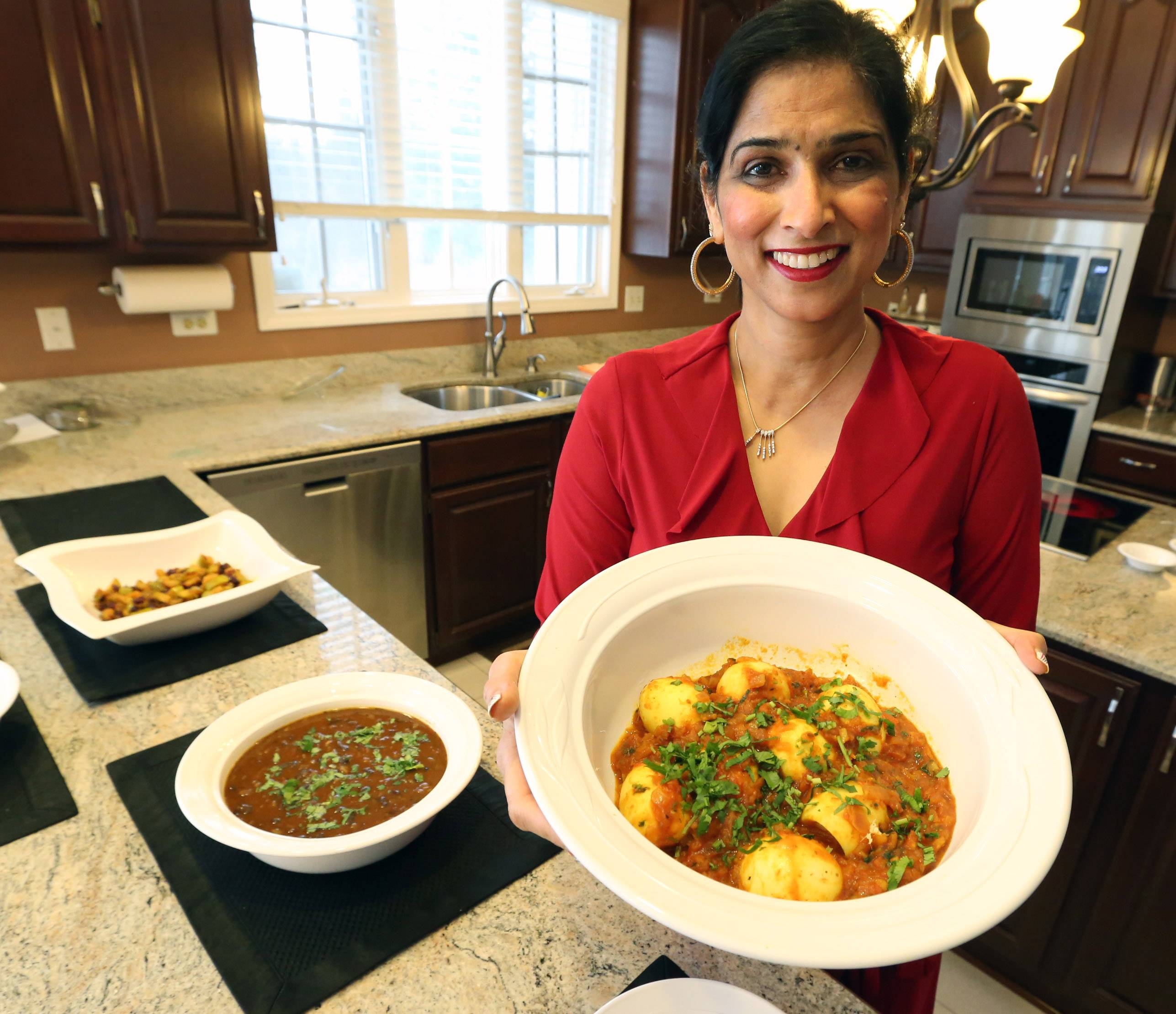 Cook of the Week Sushma Bhanot enjoys introducing friends to homemade Indian cuisine, like curry eggs, from right, curry red kidney beans and an sweet-savory fruit dish called sabzi. See her recipe for curry eggs at dailyherald.com/lifestyle/food.