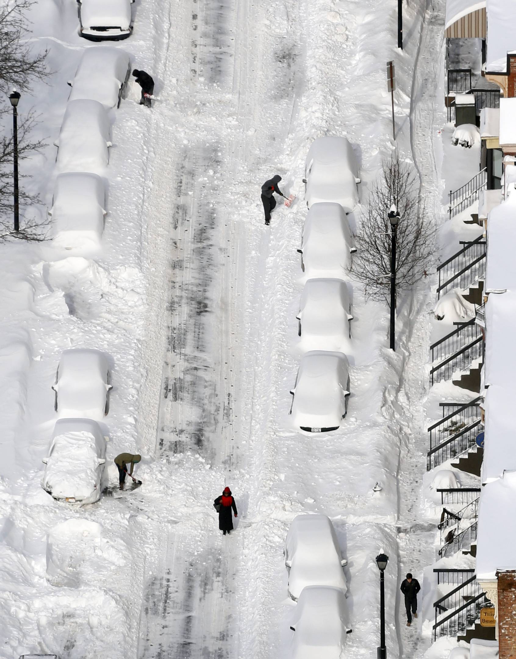 People dig out vehicles buried in snow in downtown Albany, N.Y., on Friday, Feb. 14, 2014. Schools are closed across a swath of eastern New York from the mid-Hudson Valley to the Albany ar