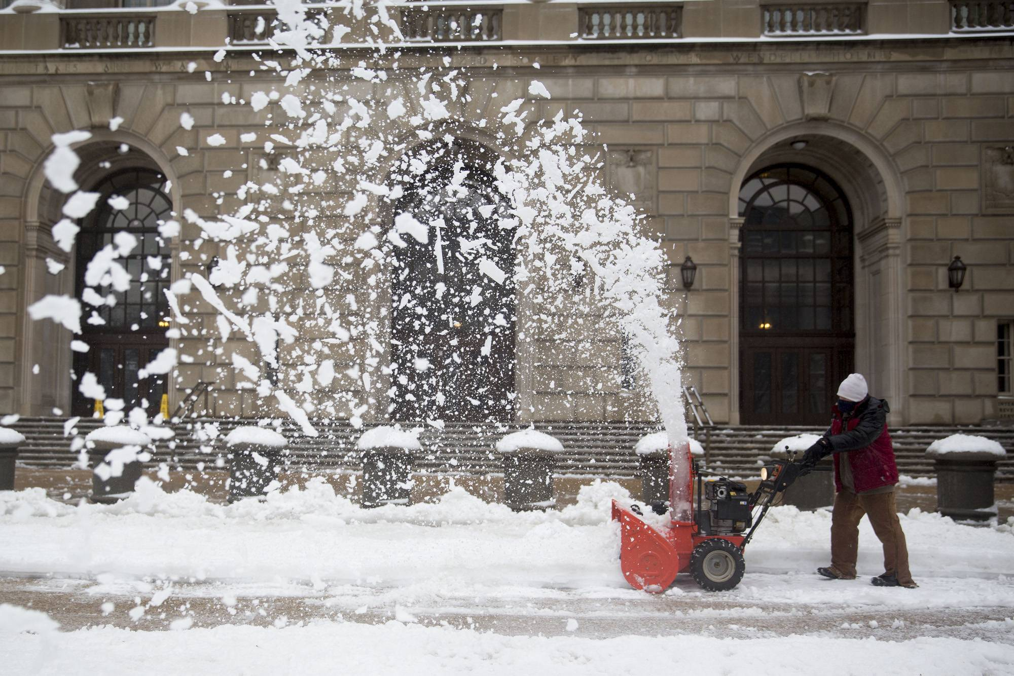 A worker uses a snowblower outside the Internal Revenue Service (IRS) in Washington, D.C., U.S., on Thursday, Feb. 13, 2014. The winter storm that cut electricity to more than half a million customers across the South and grounded 10,000 flights this week turned its power on the U.S. Northeast, bringing heavy snow from Virginia to Maine.