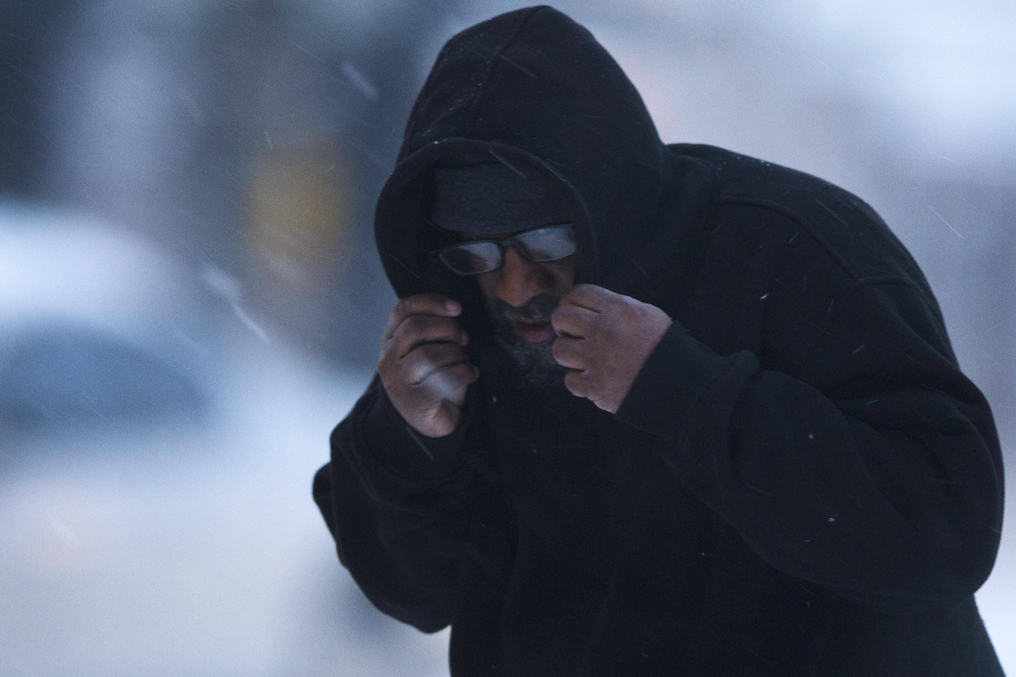 A man shields his face from a mixed winter precipitation Thursday, Feb. 13, 2014, in Philadelphia. Snow and sleet are falling on the East Coast, from North Carolina to New England, a day after sleet, snow and ice bombarded the Southeast.