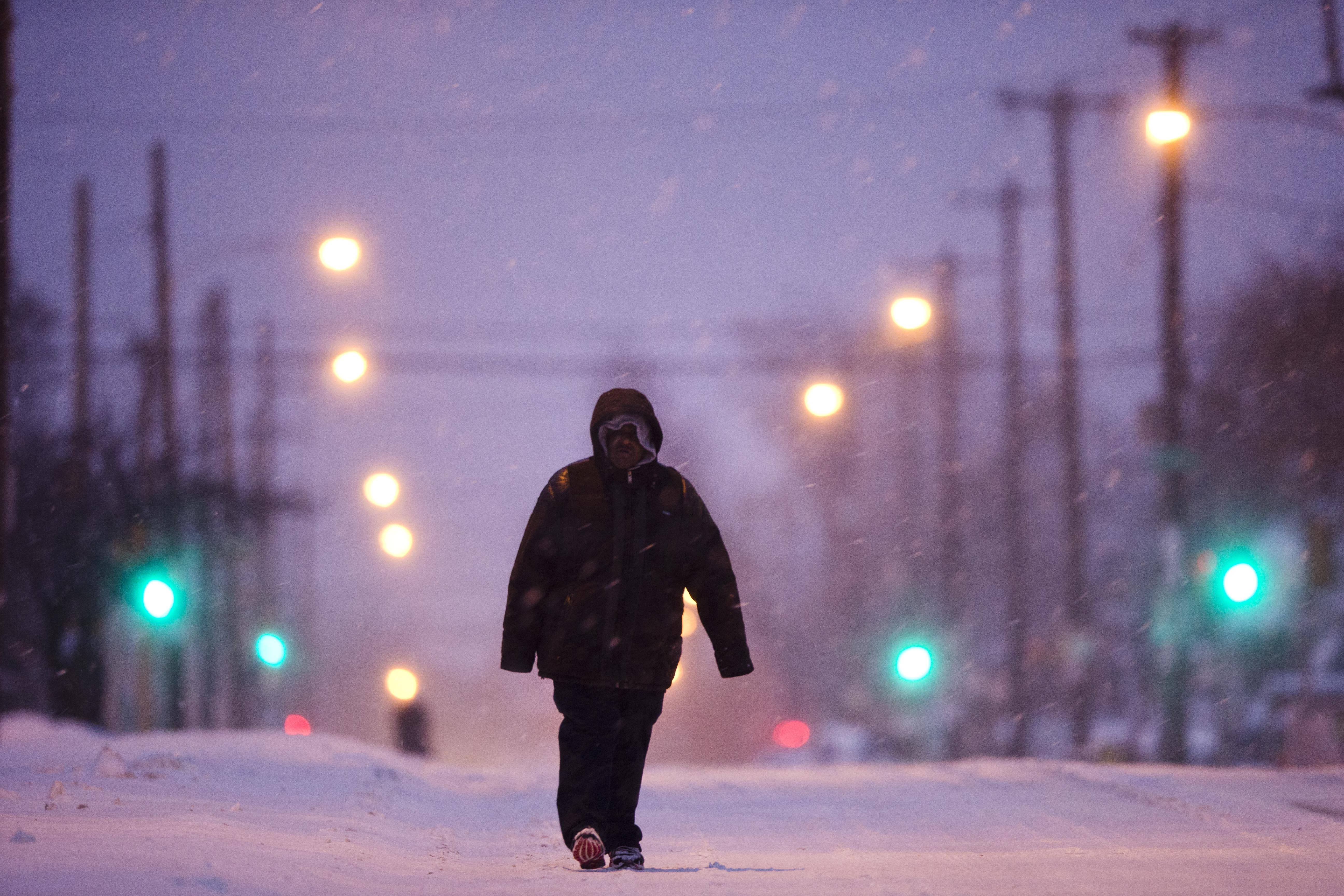 A morning commuter walks a plowed road as mixed winter precipitation falls Thursday, Feb. 13, 2014, in Philadelphia. Snow and sleet are falling on the East Coast, from North Carolina to New England, a day after sleet, snow and ice bombarded the Southeast.