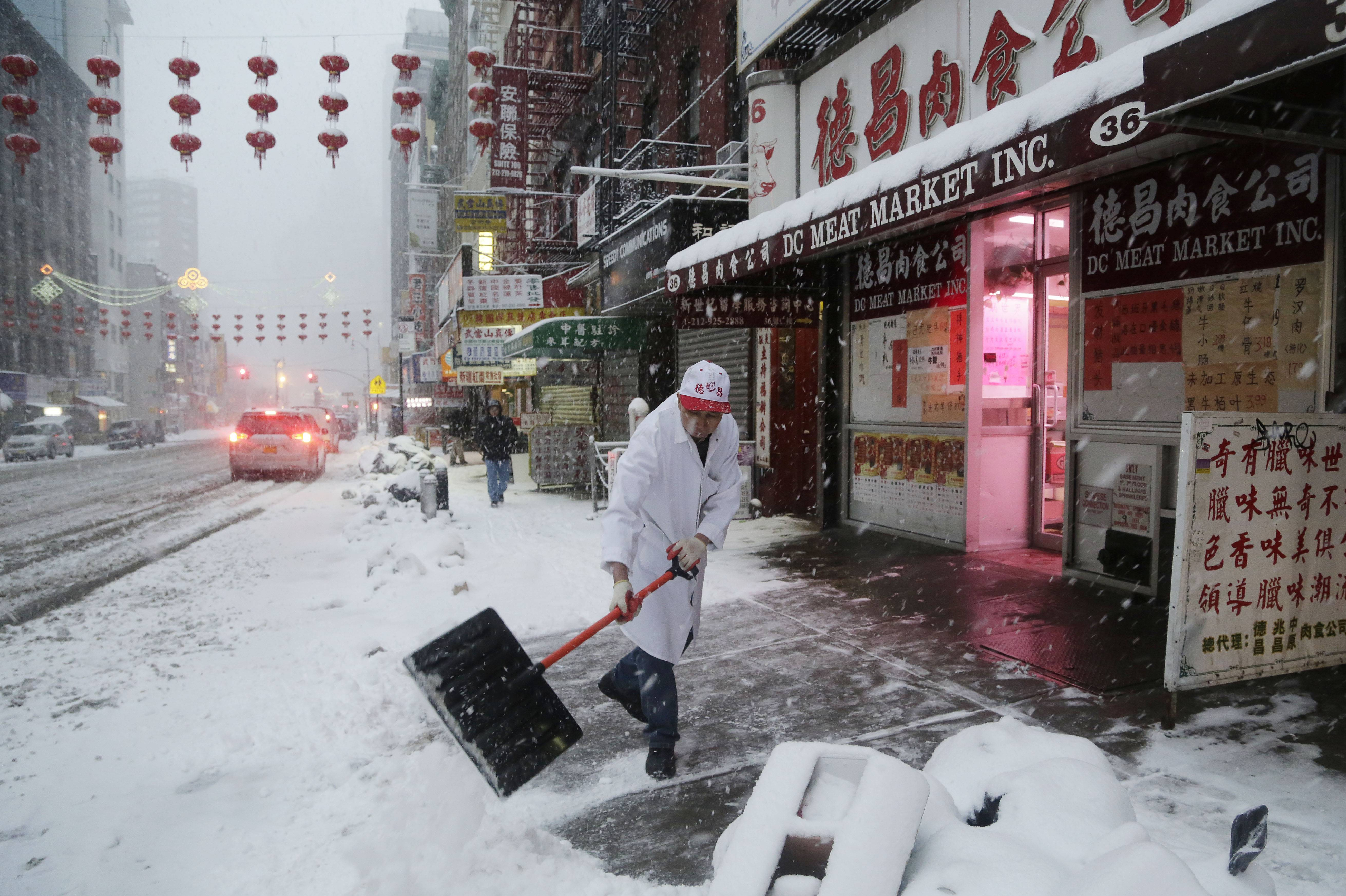 A man clears snow in front of the DC Meat Market in the Chinatown neighborhood of New York, Thursday, Feb. 13, 2014. Snow and sleet are falling on the East Coast, from North Carolina to New England, a day after sleet, snow and ice bombarded the Southeast.
