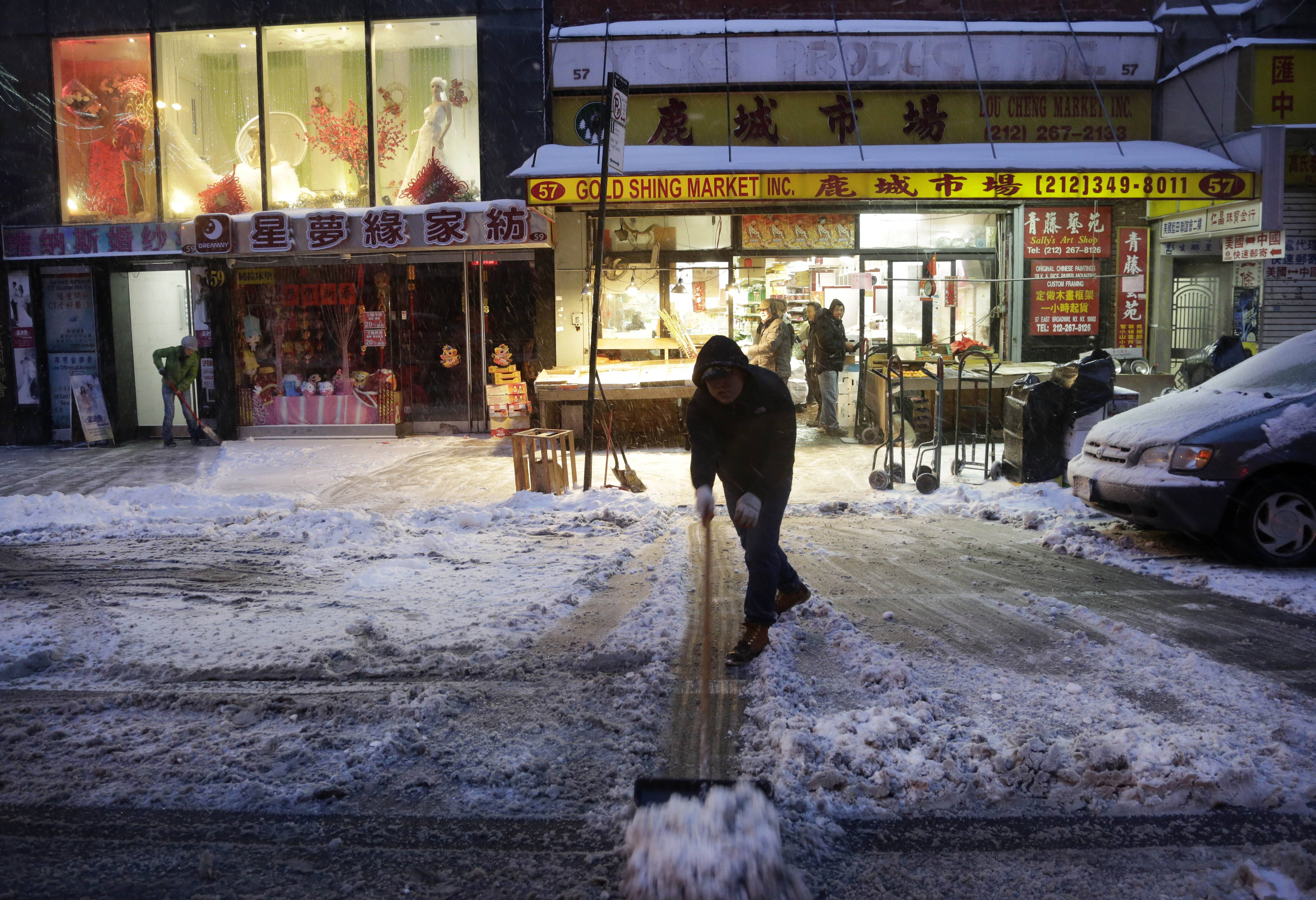 A man clears snow in front of the Gold Shing Market in the Chinatown neighborhood of New York, Thursday, Feb. 13, 2014. Snow and sleet are falling on the East Coast from North Carolina to New England a day after sleet, snow and ice bombarded the Southeast.