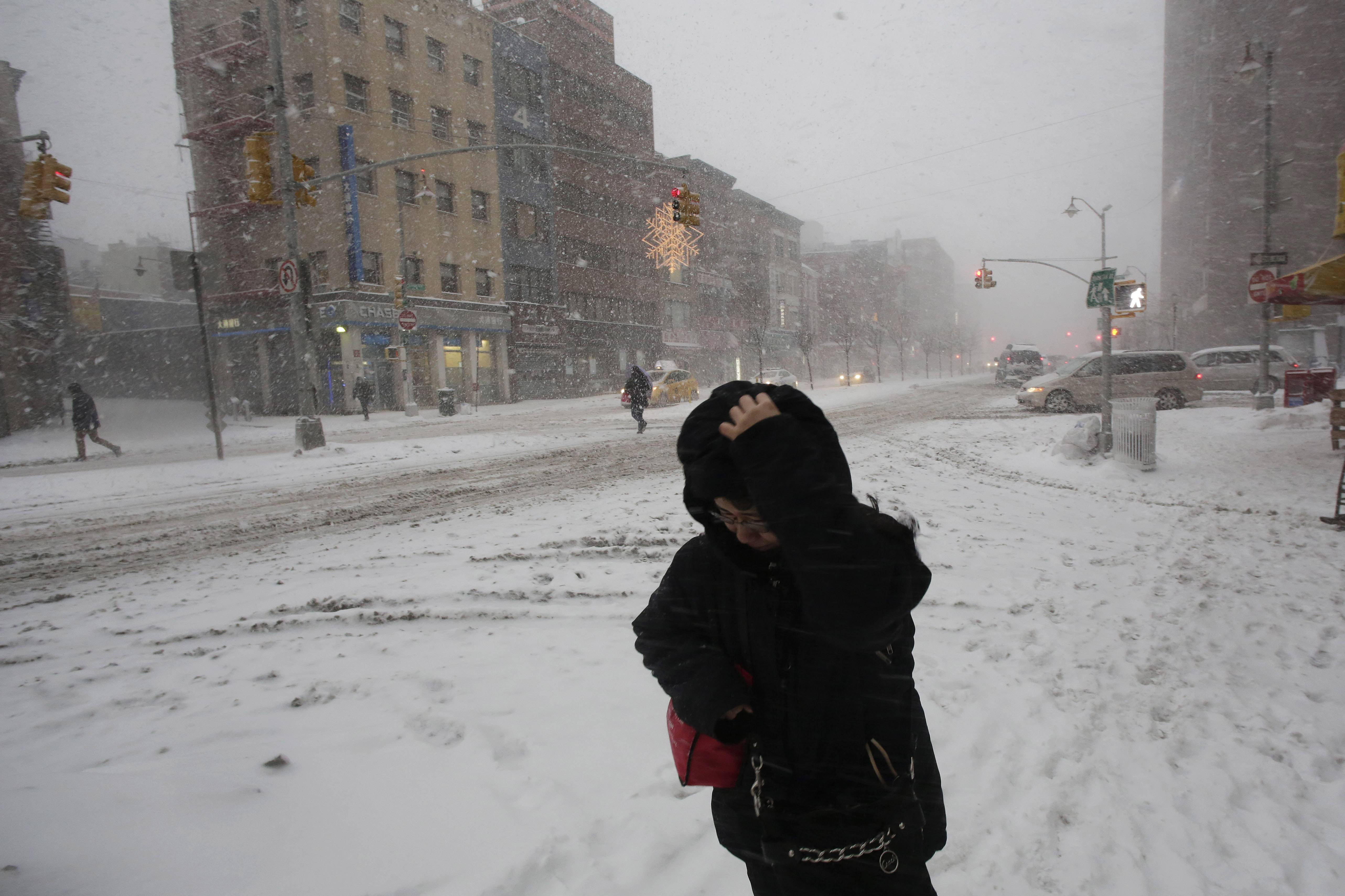 A woman walks through the snow in the Chinatown neighborhood of New York, Thursday, Feb. 13, 2014. Snow and sleet are falling on the East Coast, from North Carolina to New England, a day after sleet, snow and ice bombarded the Southeast.