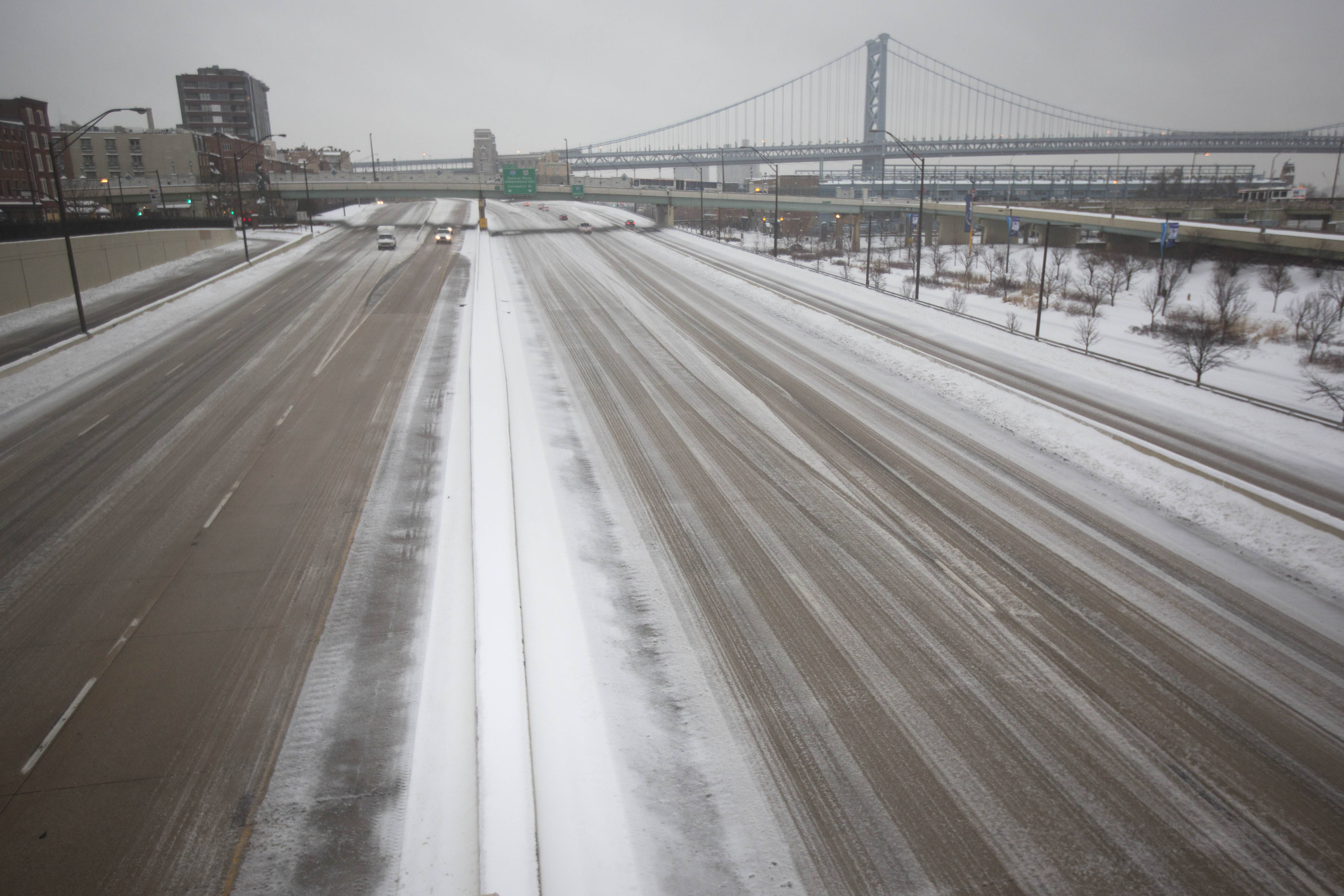 Interstate 95 remains largely untraveled as mixed winter precipitation falls, Thursday, Feb. 13, 2014, in Philadelphia. Snow and sleet are falling on the East Coast, from North Carolina to New England, a day after sleet, snow and ice bombarded the Southeast.
