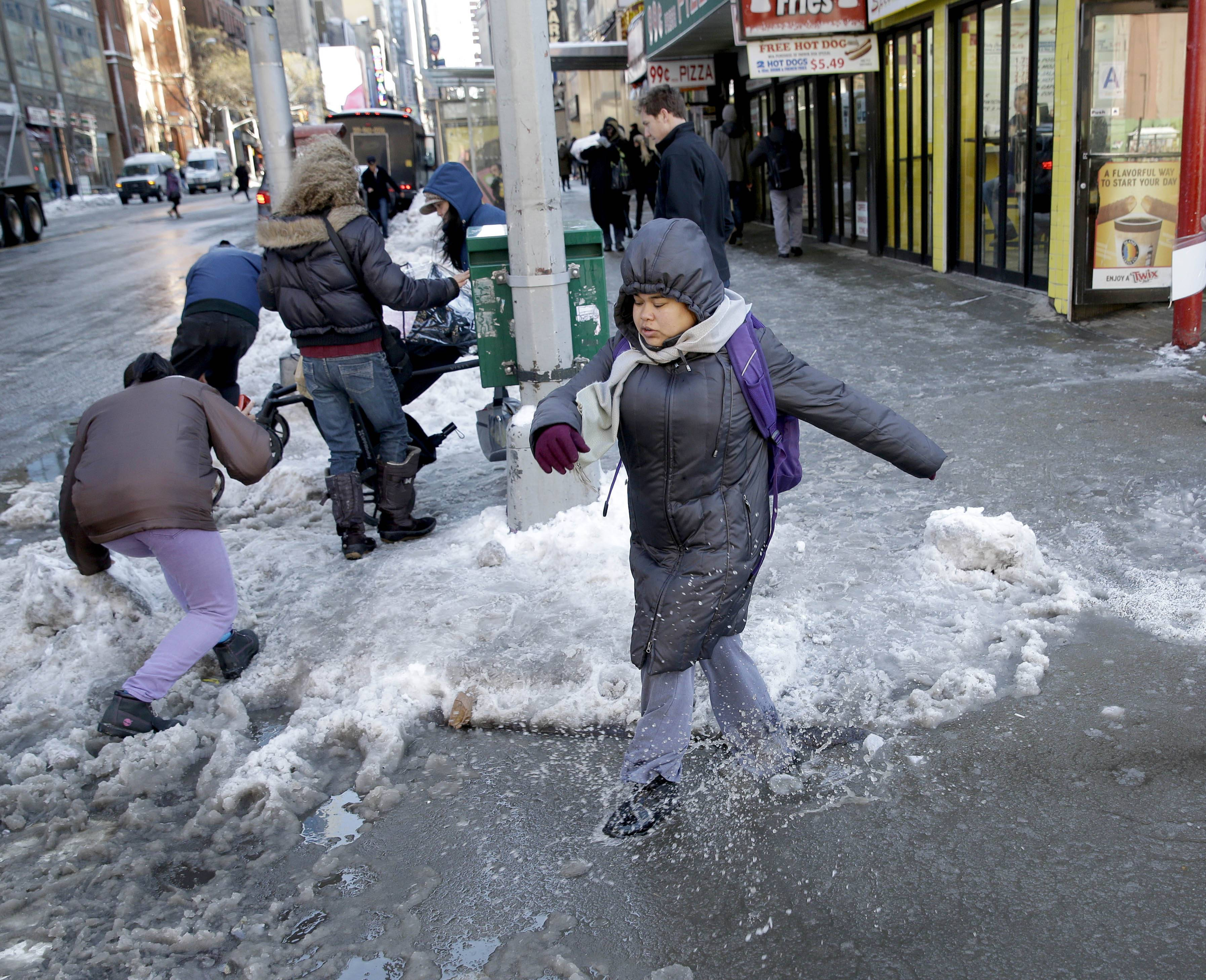 Pedestrians struggle to navigate a slushy intersection in New York, Friday, Feb. 14, 2014. Commuters faced slick roads on Friday after yet another winter storm brought snow and ice to the East Coast, leaving at least 24 people dead.