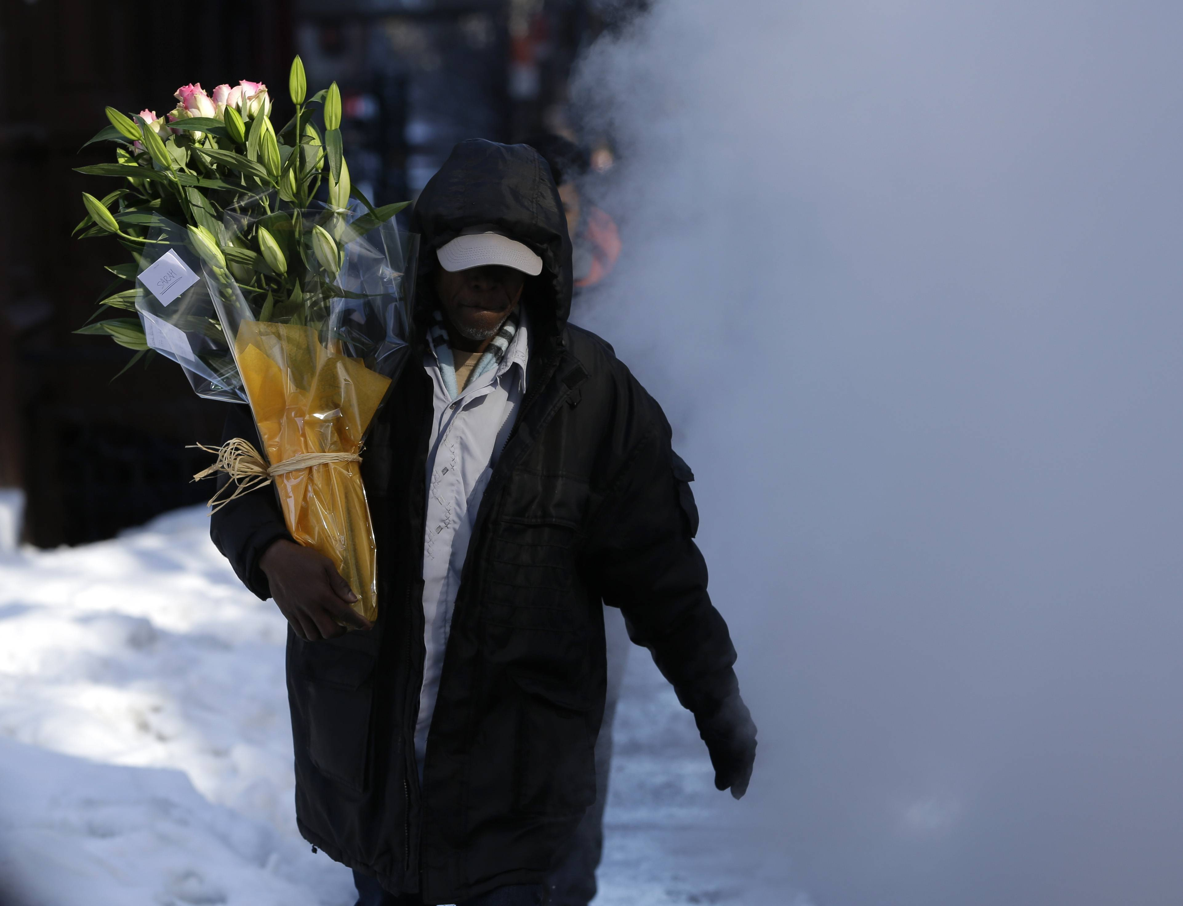 A man delivering flowers walks through a cloud of steam on a snowy street in New York, Friday, Feb. 14, 2014. Commuters faced slick roads on Friday after yet another winter storm brought snow and ice to the East Coast, leaving at least 24 people dead.