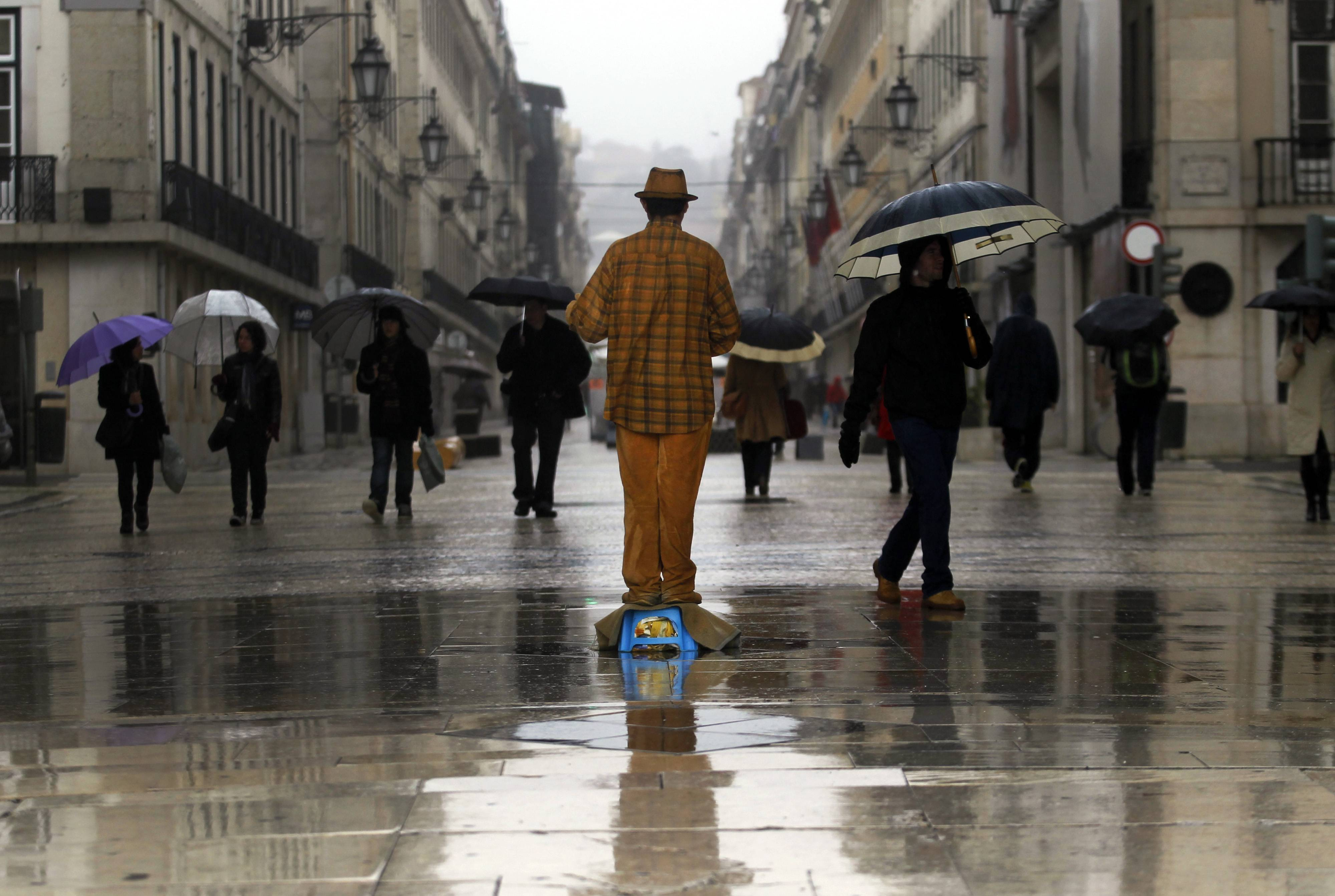 A street artist performs as passers-by shelter against the rain with umbrellas in downtown Lisbon, Tuesday, Feb. 11, 2014.
