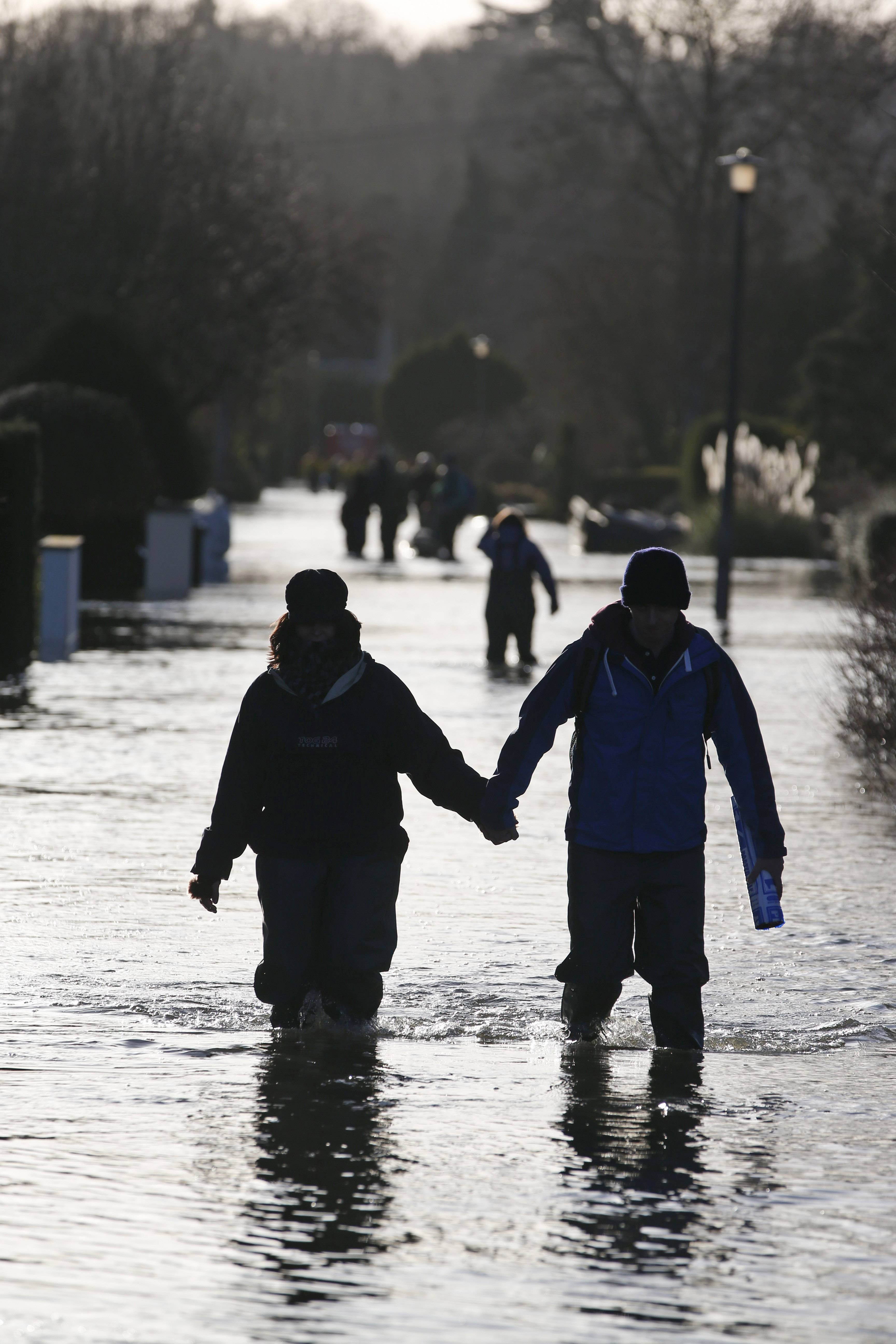 Residents walk in the flooded village of Wraysbury, England, Tuesday, Feb. 11, 2014. British Prime Minister David Cameron says that money is no object in the fight against the mass flooding that has hit parts of England and that he is canceling his visit to the Middle East to oversee the effort.