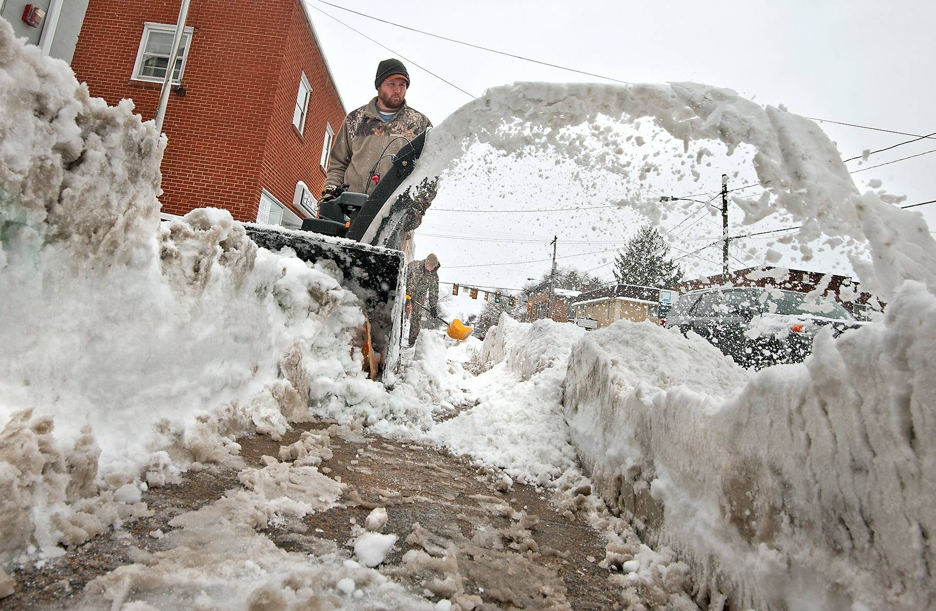 Grant French blows snow while his brother, Ross, follows with a shovel along Main Street in Bridgewater, Va., Thursday, Feb. 13, 2014.