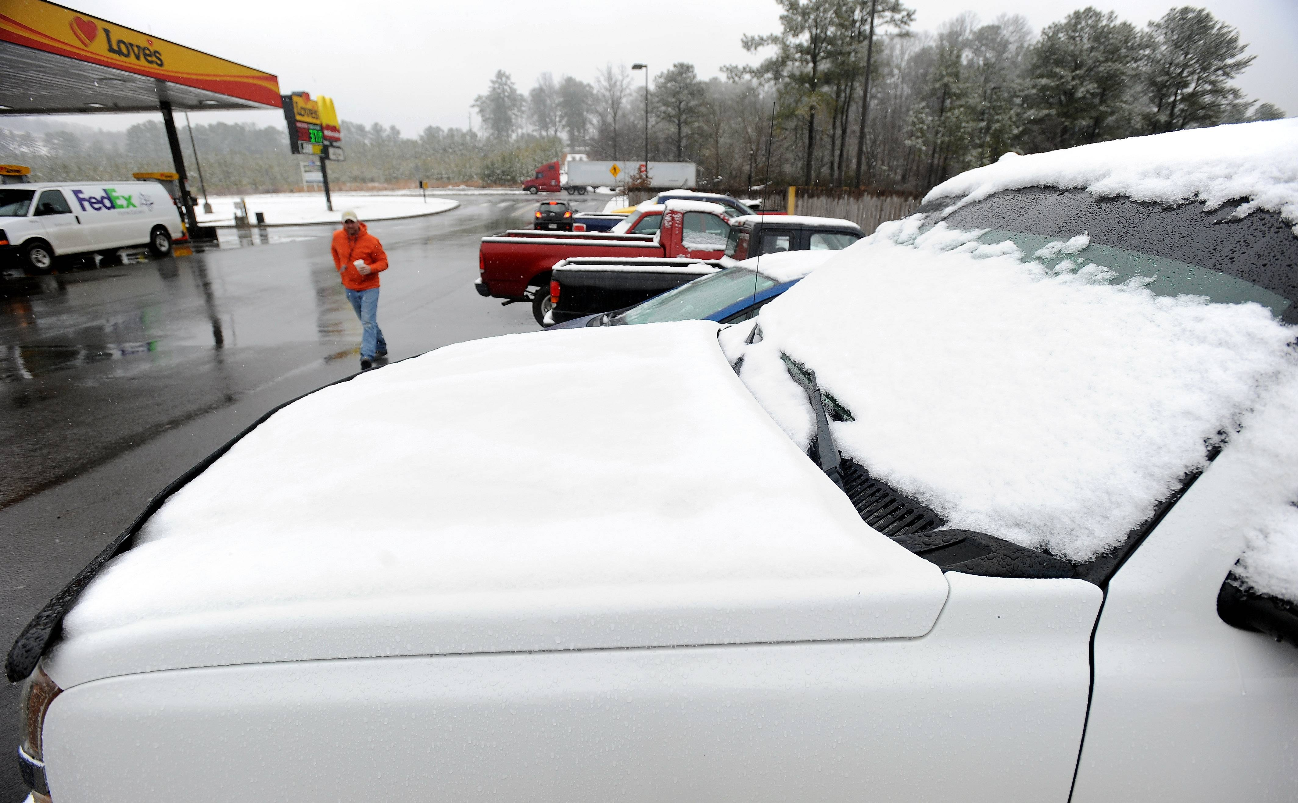 Snow accumulates on a pickup truck as Ryan Warmack, center, walks toward a truck stop trying to locate tire chains during a winter snowstorm in Emerson, Ga., about 40 miles north of metro Atlanta, on Tuesday, Feb. 11, 2014.