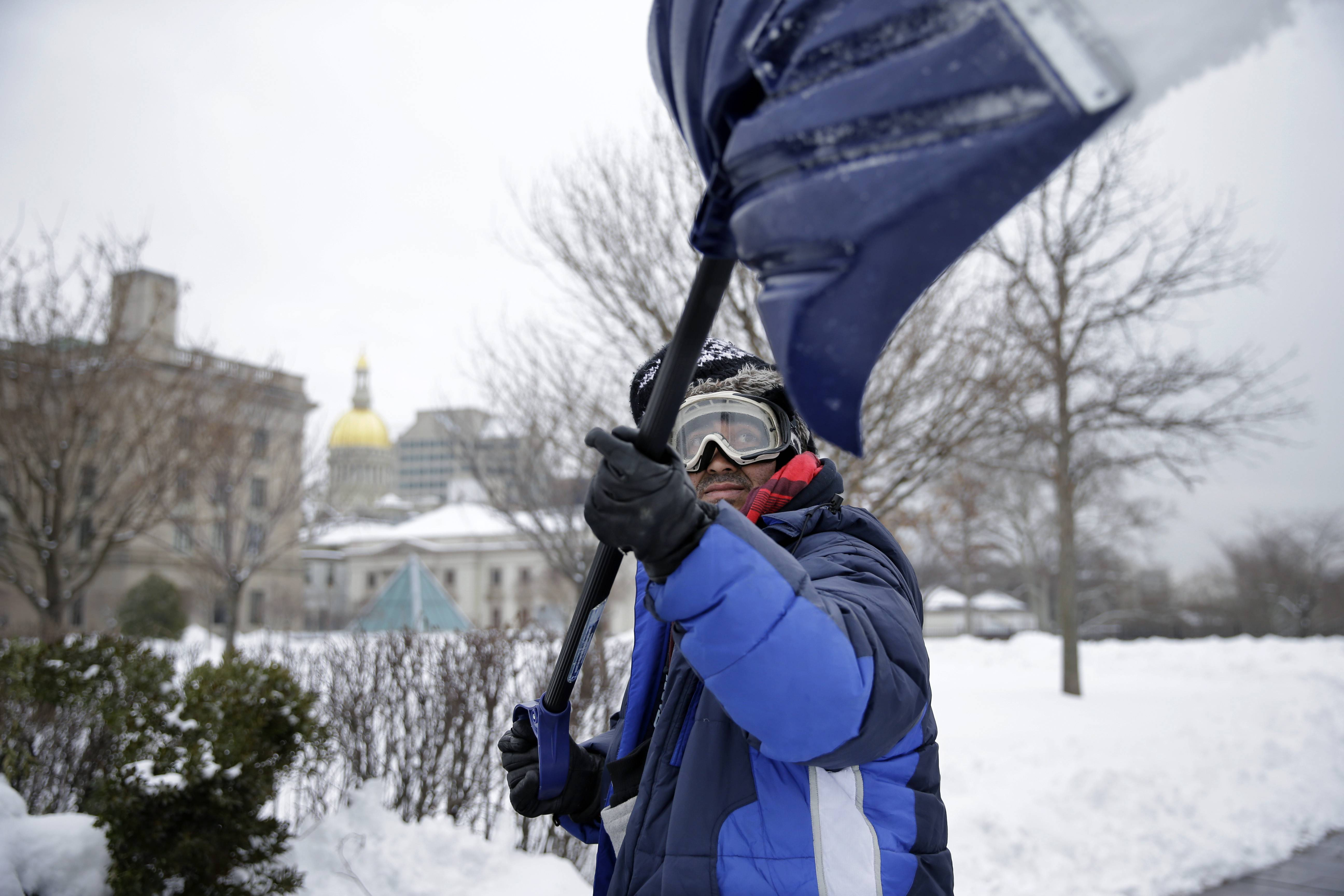 "Marco Garcia, of Guatemala, shovels snow near the Statehouse in Tuesday, Feb. 18, 2014, in Trenton, N.J., after a quick-moving storm brought several inches of snow as well as rare ""thundersnow"" to parts of the winter-weary East Coast."