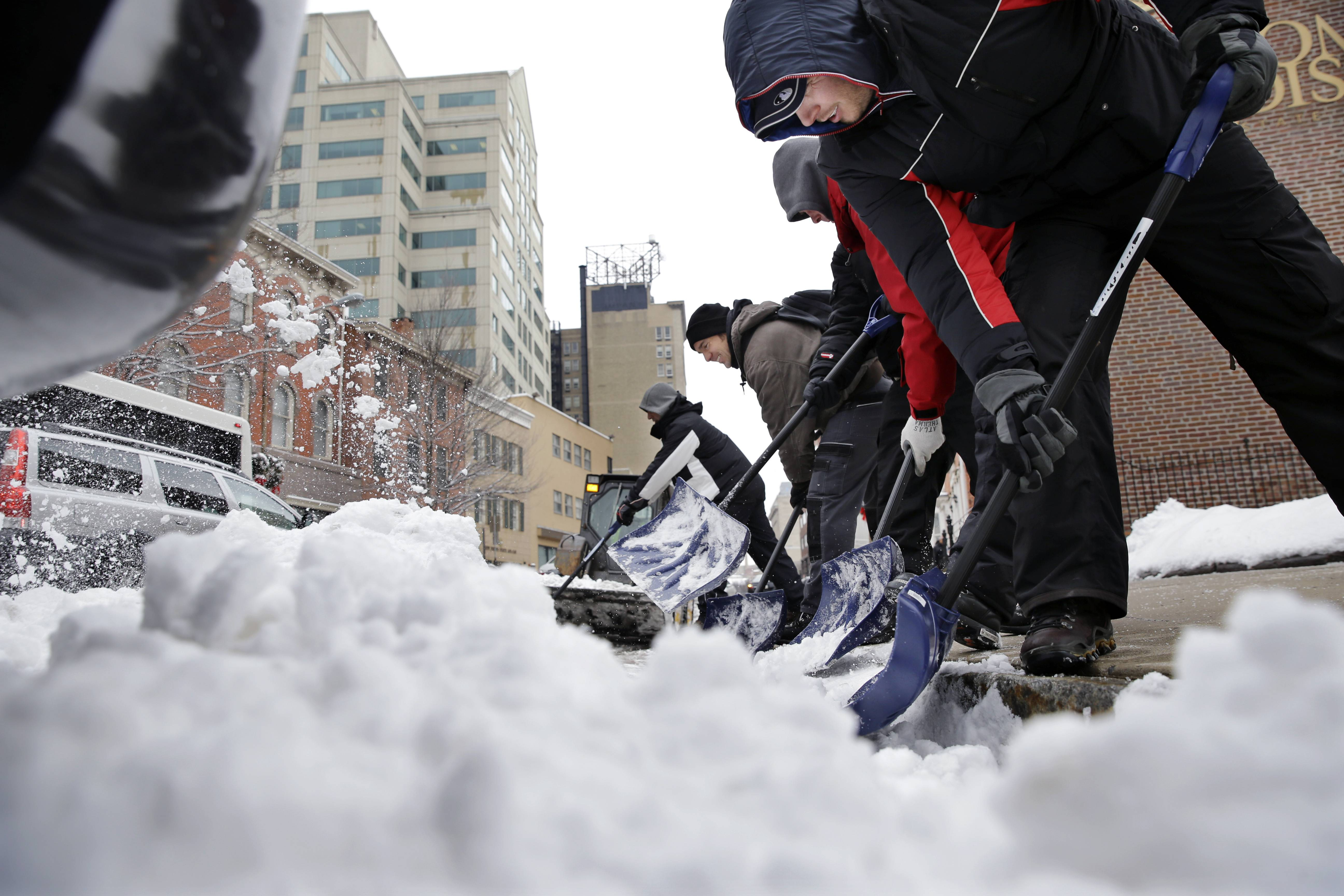 "Workers clear newly-fallen snow from a street, Tuesday, Feb. 18, 2014, in Trenton, N.J., after a quick-moving storm brought several inches of snow as well as rare ""thundersnow"" to parts of the winter-weary East Coast."