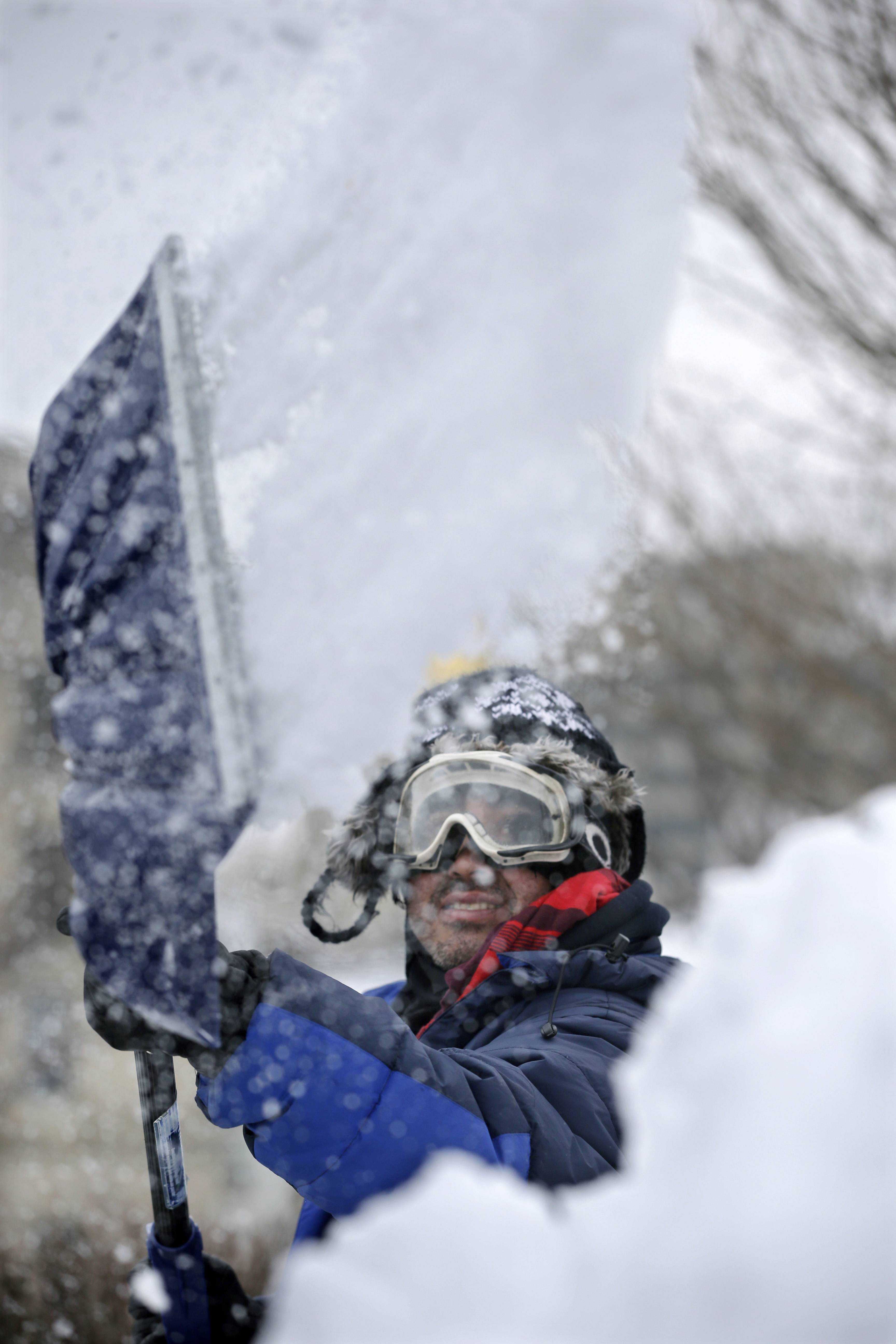 "Marco Garcia, of Guatemala, shovels snow Tuesday, Feb. 18, 2014, in Trenton, N.J., after a quick-moving storm brought several inches of snow as well as rare ""thundersnow"" to parts of the winter-weary East Coast."