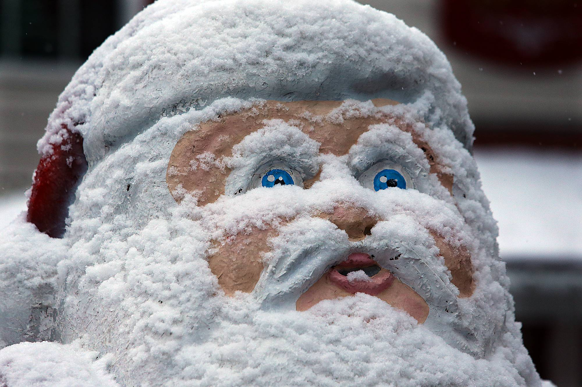 A Santa Claus statue displayed outside The Christmas Shoppe sports a frozen face as it becomes covered in snow on Tuesday, Feb. 11, 2014, in Helen, Ga.