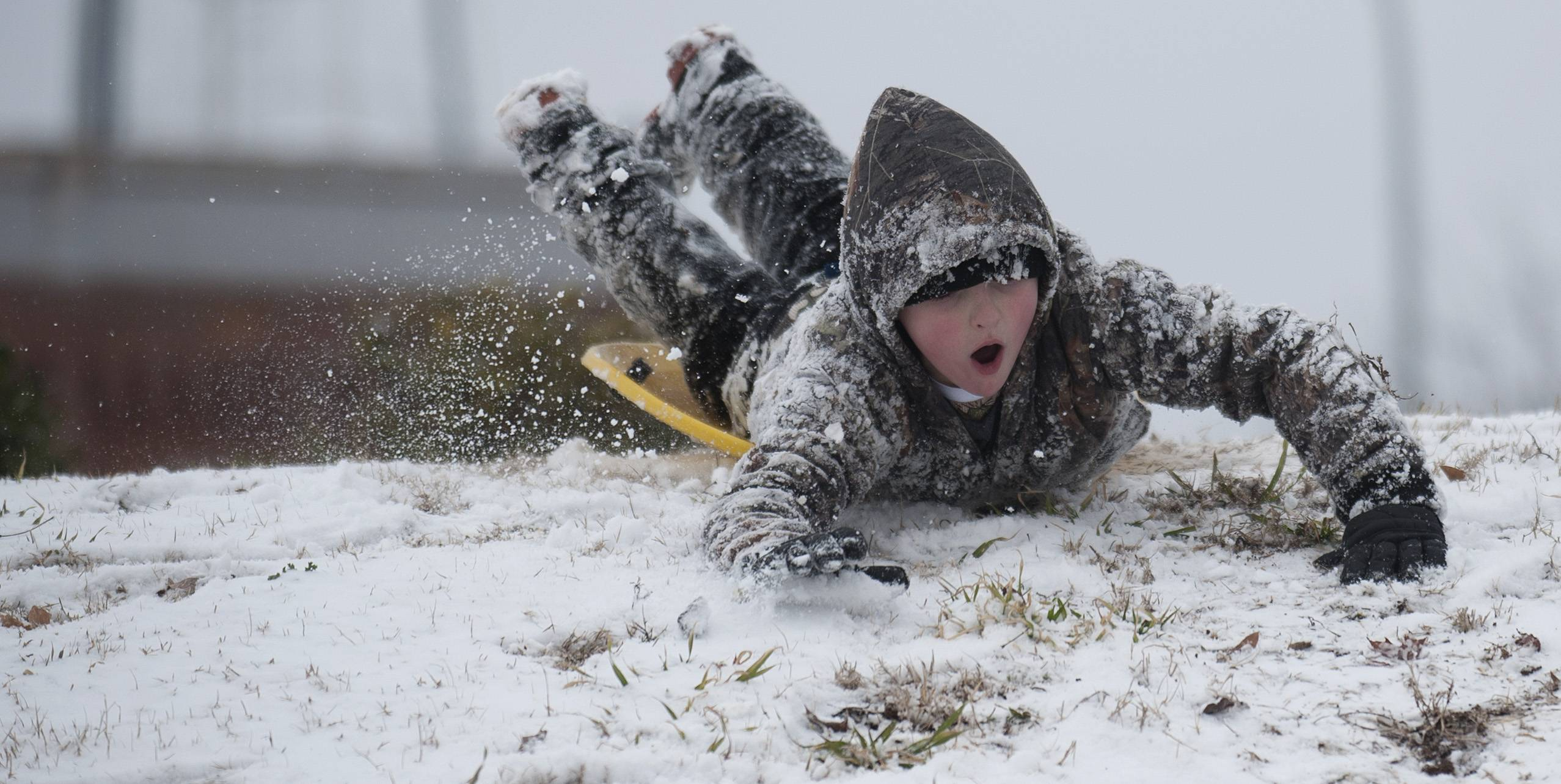 Jackson Sherrill slides down a hill at Founder Park in Decatur, Ala., on Tuesday, Feb. 11, 2014. A winter storm dropped several inches of snow on North Alabama overnight and more is expected.