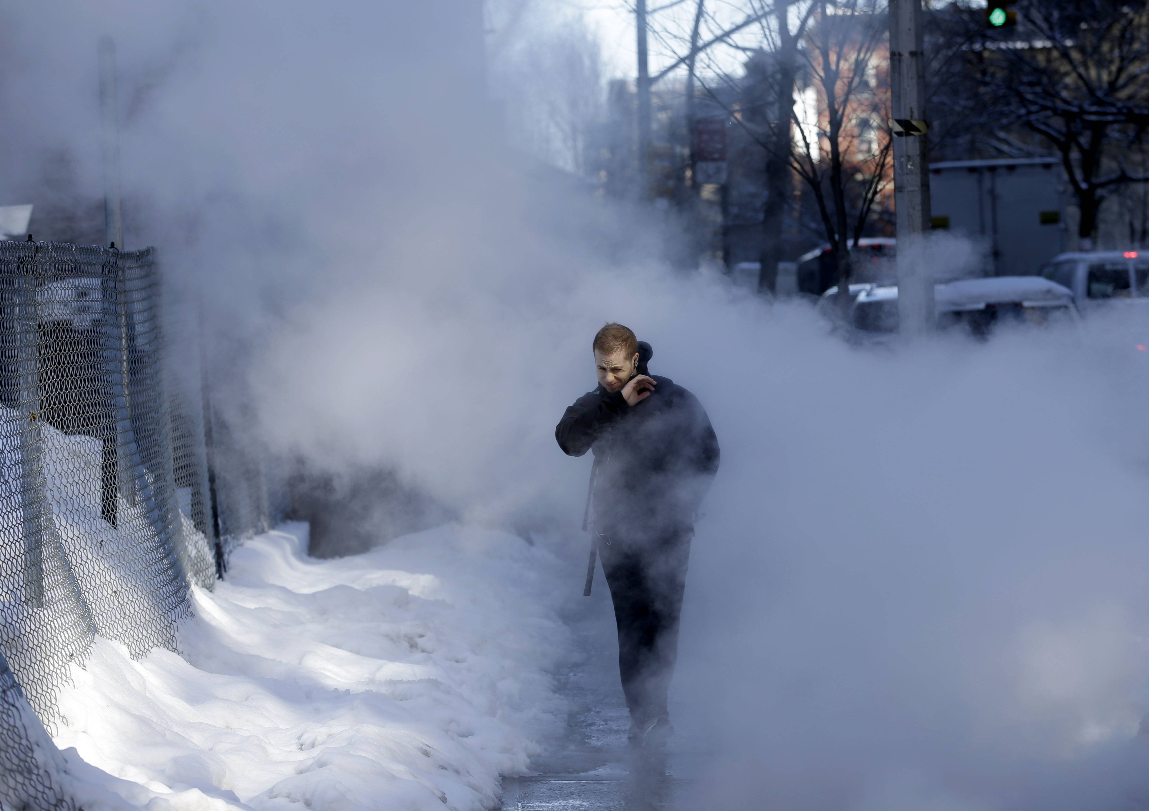 A pedestrian walks through a cloud of steam on a snowy street in New York, Friday, Feb. 14, 2014. Commuters faced slick roads on Friday after yet another winter storm brought snow and ice to the East Coast, leaving at least 24 people dead.