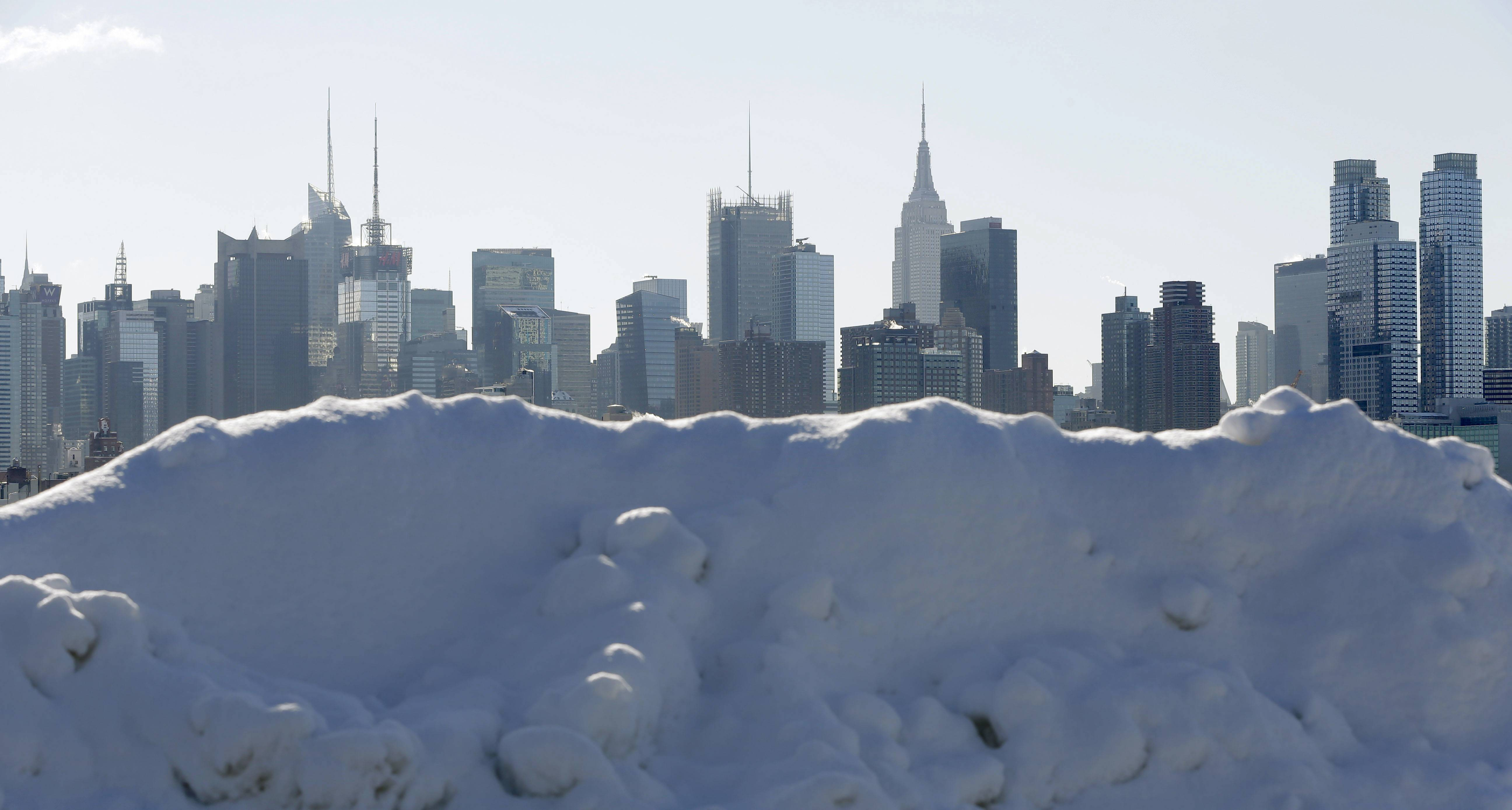 Piles of snow line the waterfront overlooking the New York City skyline in Weehawken, N.J., Friday, Feb. 14, 2014. Commuters faced slick roads on Friday after yet another winter storm brought snow and ice to the East Coast, leaving at least 24 people dead.