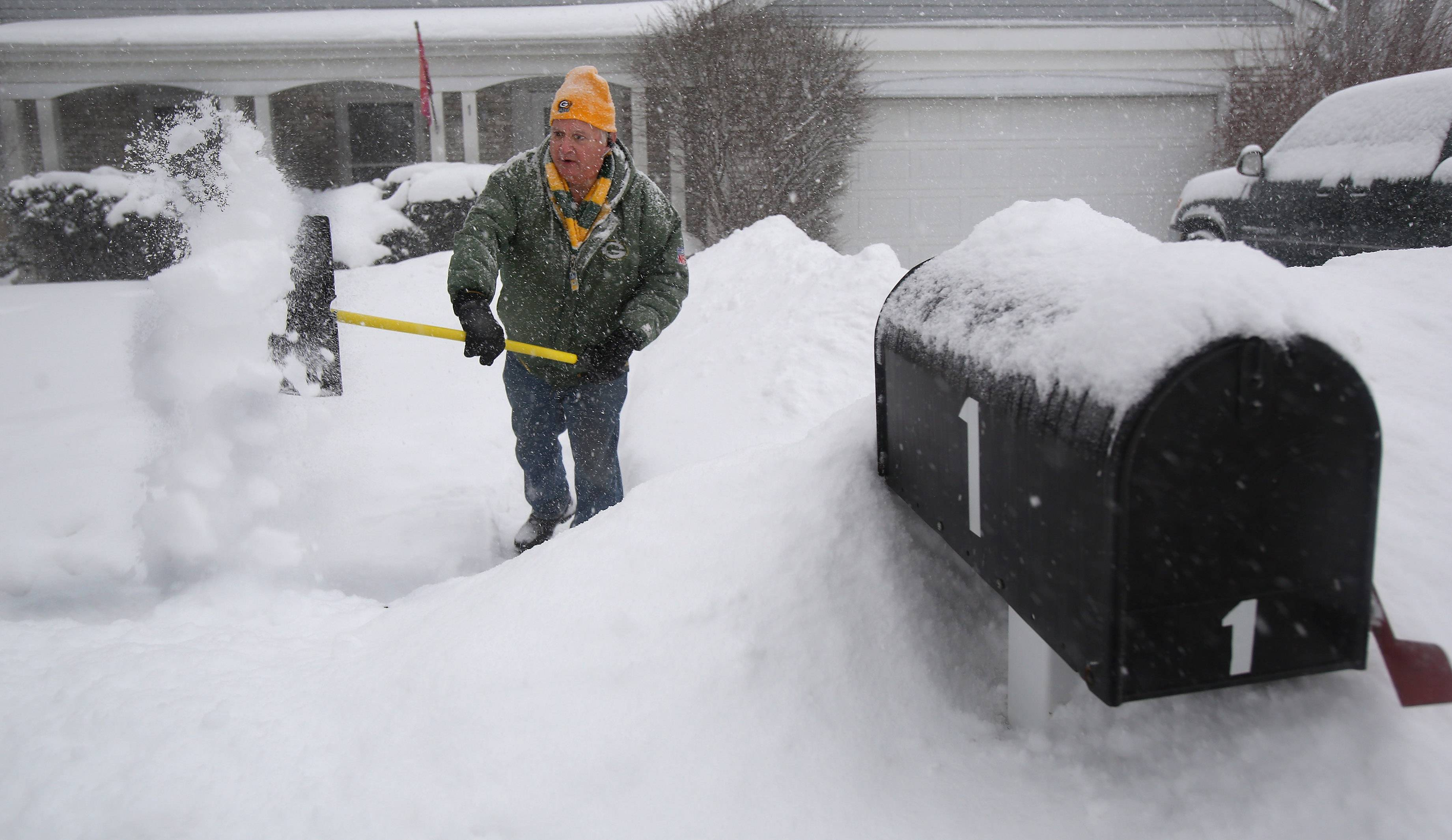Vernon Hills resident Tom Herrmann shovels his sidewalk with snow piling up around his mailbox Monday. Snow came down throughout the day in Lake County.