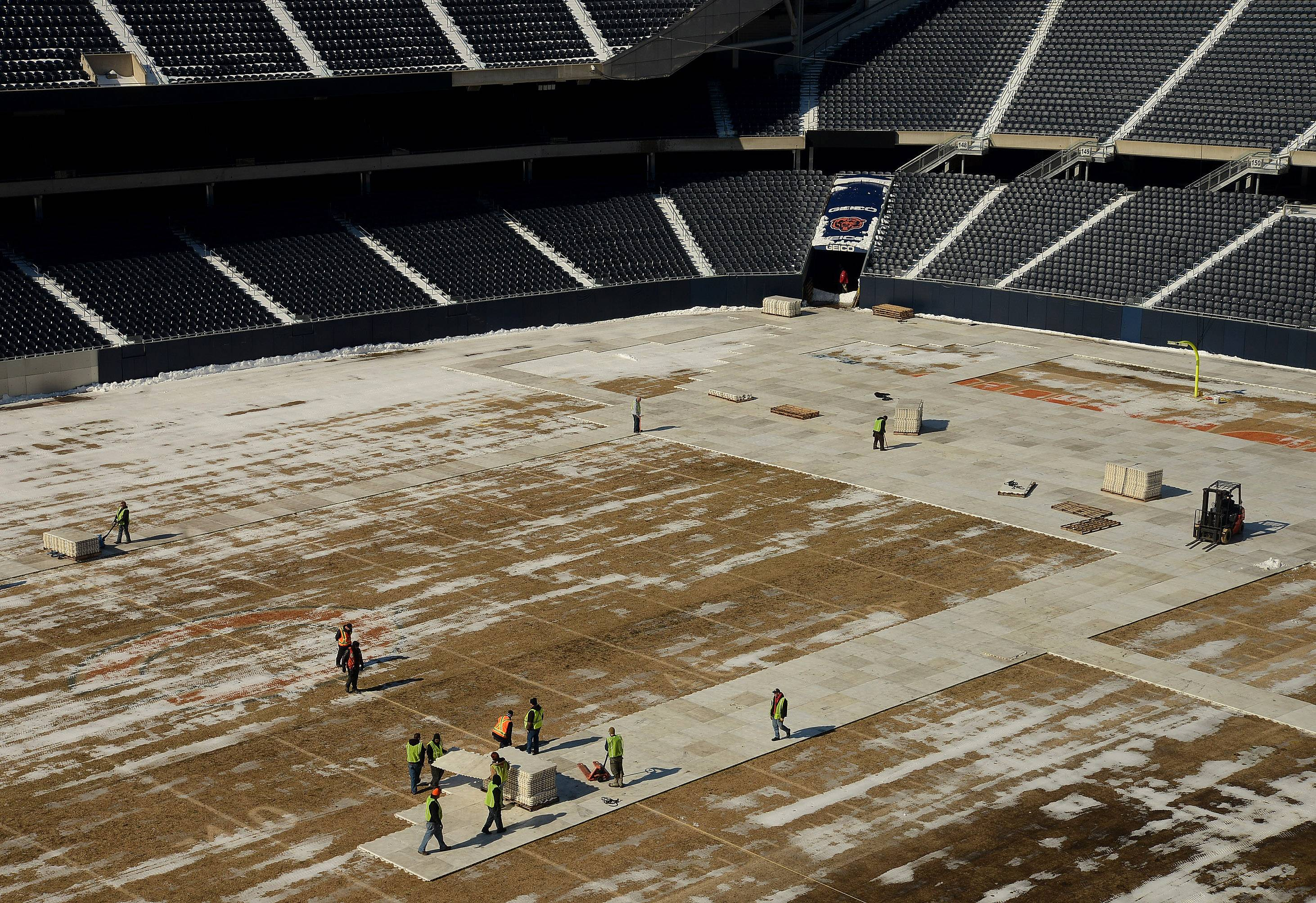 Crews start work preparing the Soldier Field gridiron for the NHL Stadium Series game between the Blackhawks and Penguins on March 1.