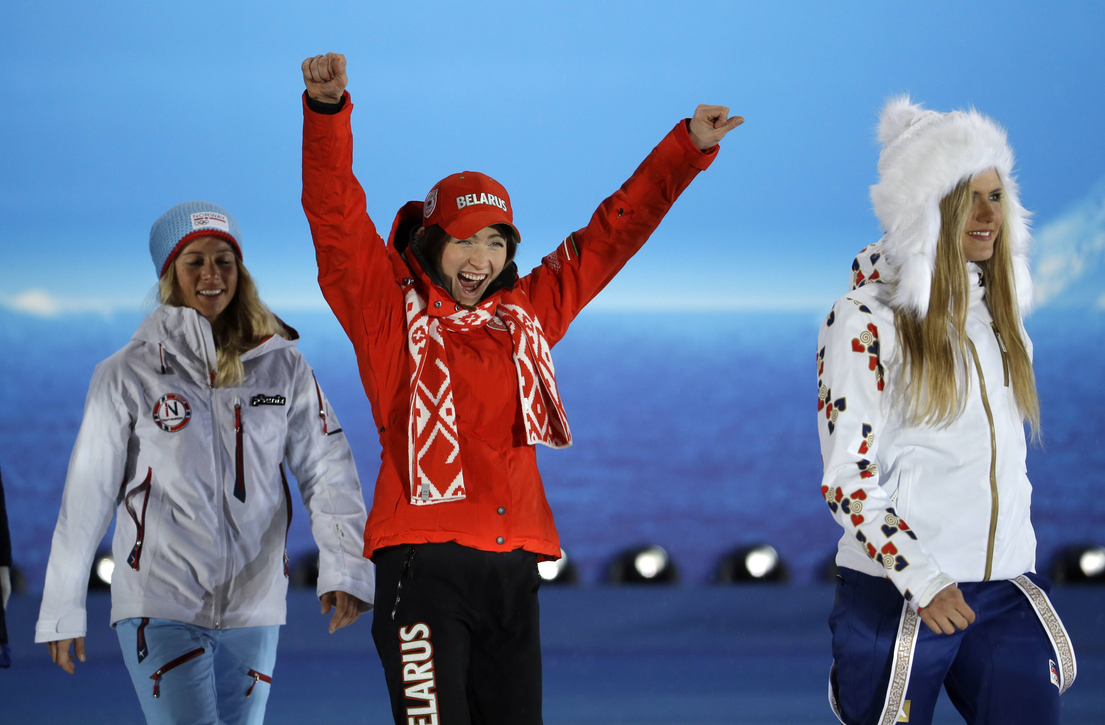 Belarus' Darya Domracheva, the gold medalist in the women's biathlon 12.5K mass start, center, celebrates while walking between bronze medalist Tiril Eckhoff of Norway, left, and silver medalist Gabriela Soukalova of the Czech Republic.