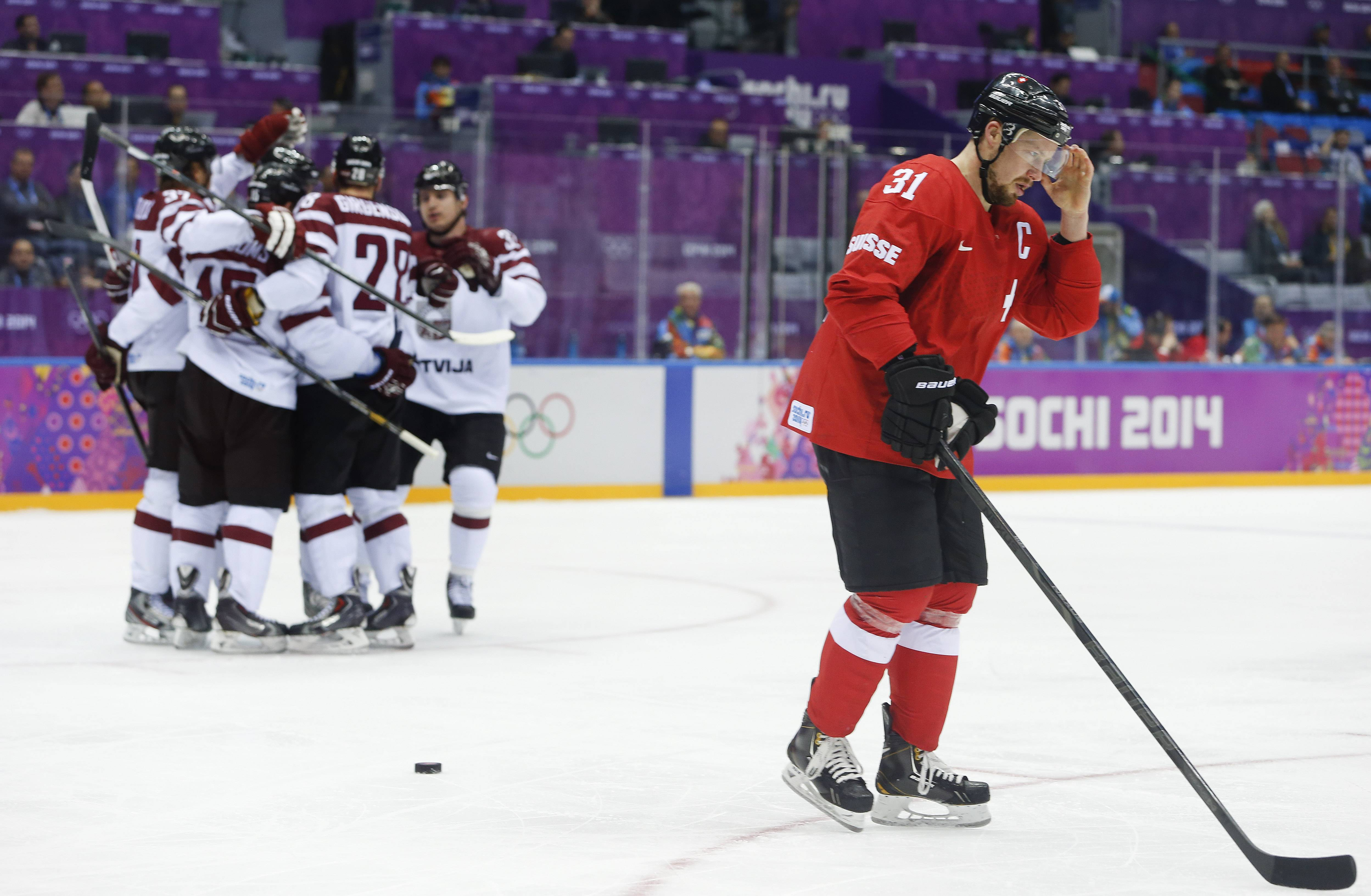 Switzerland defenseman Mathias Seger skates back to the bench after Latvia scored a goal in the first period .