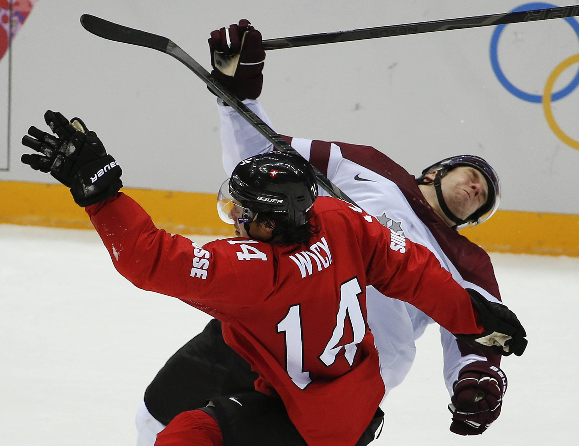 Switzerland forward Roman Wick (14) collides with Latvia forward Janis Sprukts in the second period of a men's ice hockey game at the 2014 Winter Olympics, Tuesday, Feb. 18, 2014, in Sochi, Russia.