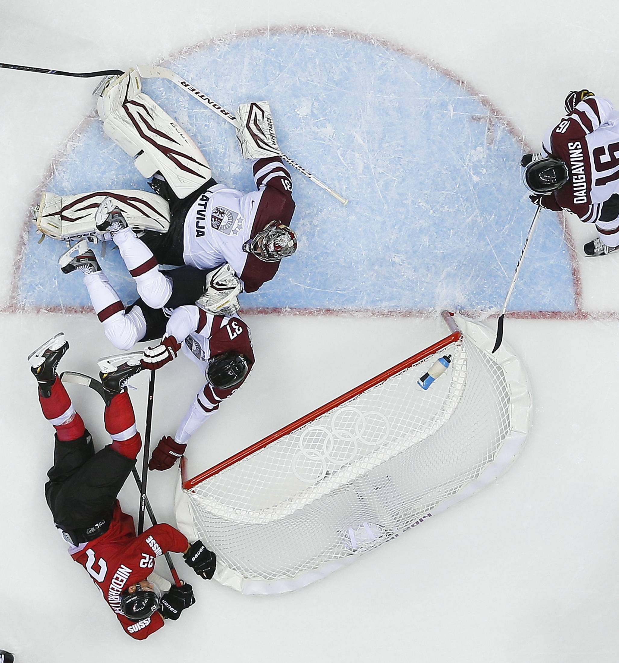 Switzerland forward Nino Niederreiter (22) collides with Latvia defenseman Oskars Bartulis and goaltender Edgars Masalskis in the third period.
