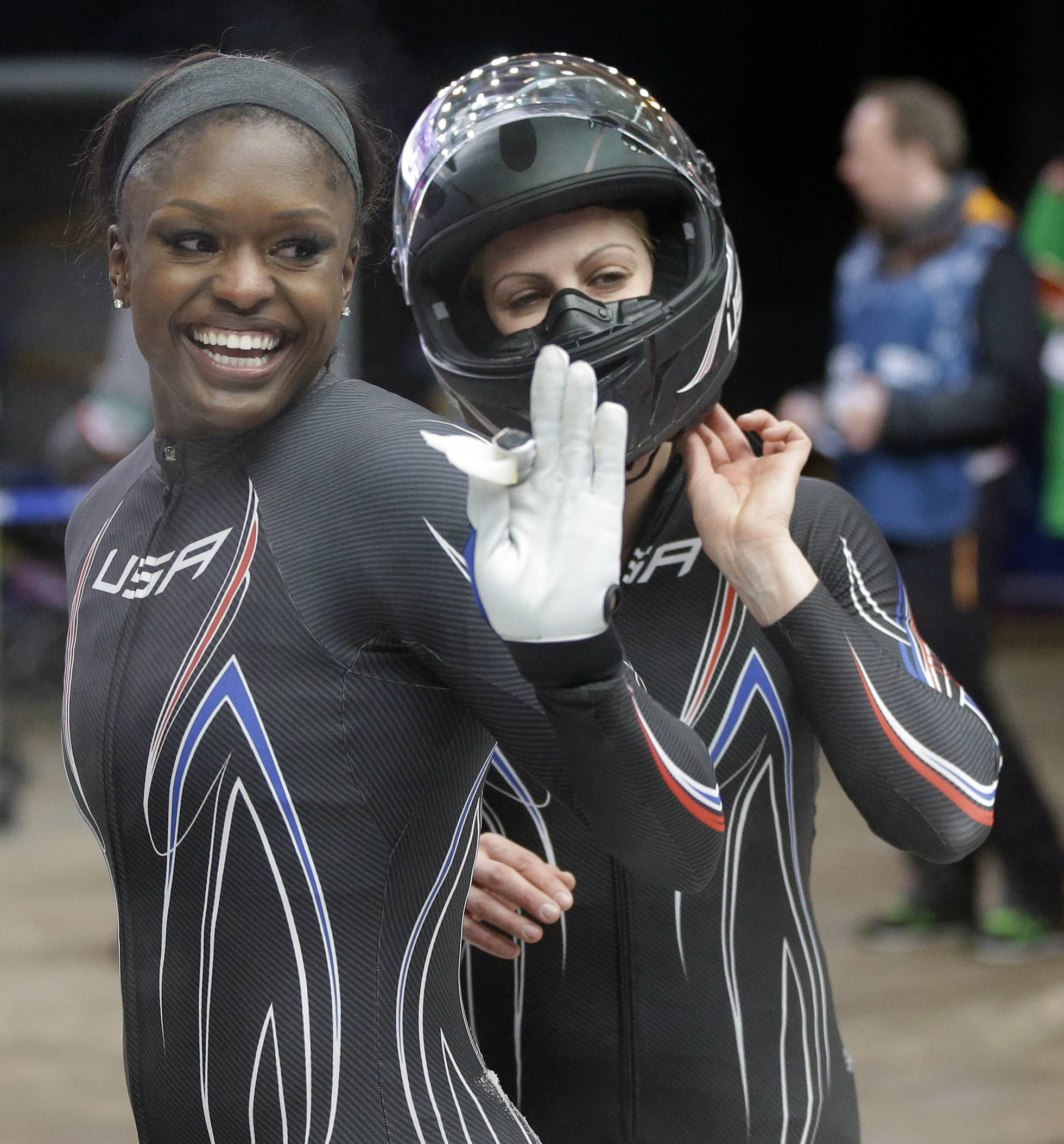 The team from the United States USA-2, piloted by Jamie Greubel with brakeman Aja Evans, left, wave to fans after their second run during the women's two-man bobsled competition.
