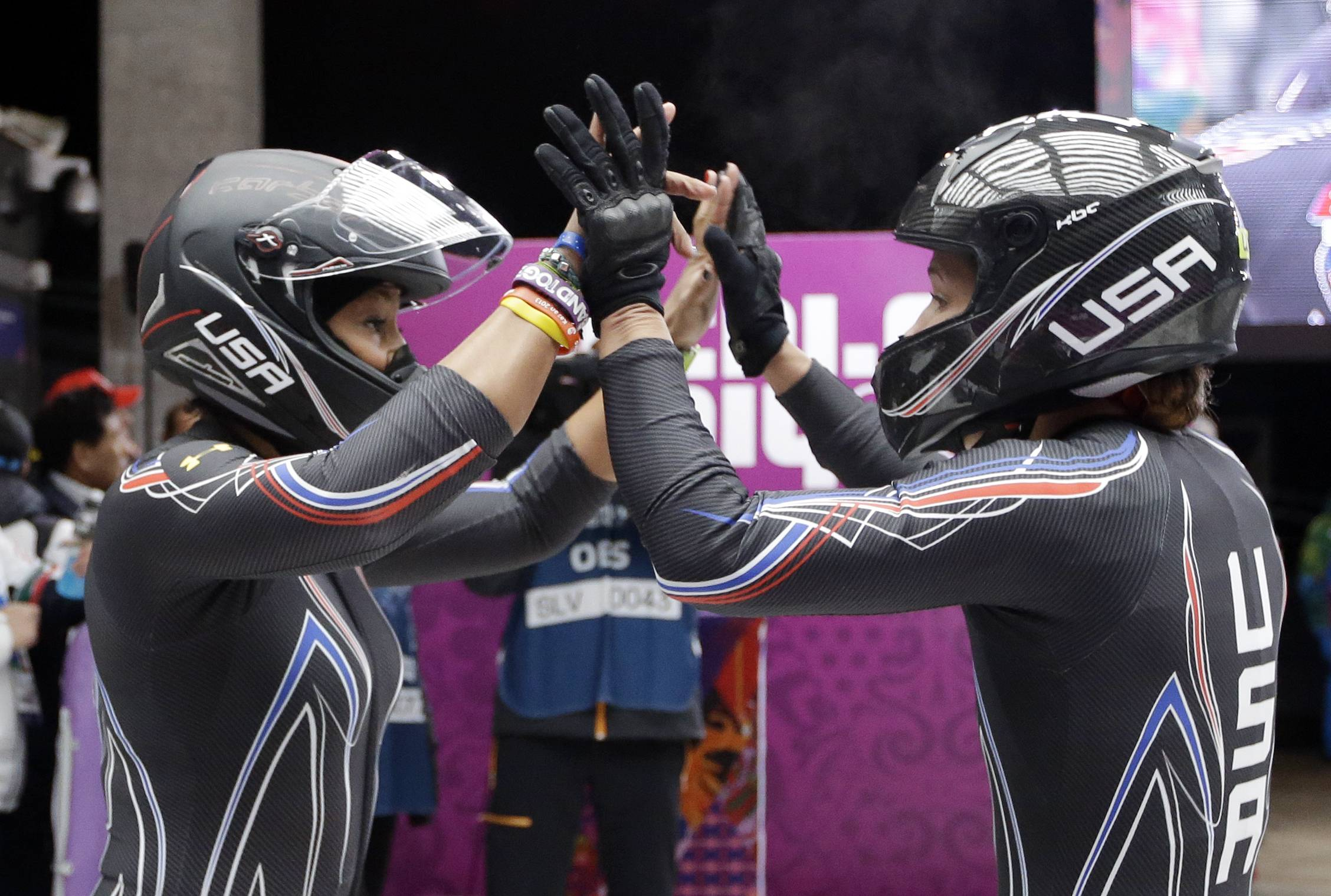 The team from the United States USA-3, piloted by Jazmine Fenlator with brakeman Lolo Jones, high-five after their first run during the women's two-man bobsled competition at the 2014 Winter Olympics, Tuesday, Feb. 18, 2014, in Krasnaya Polyana, Russia.