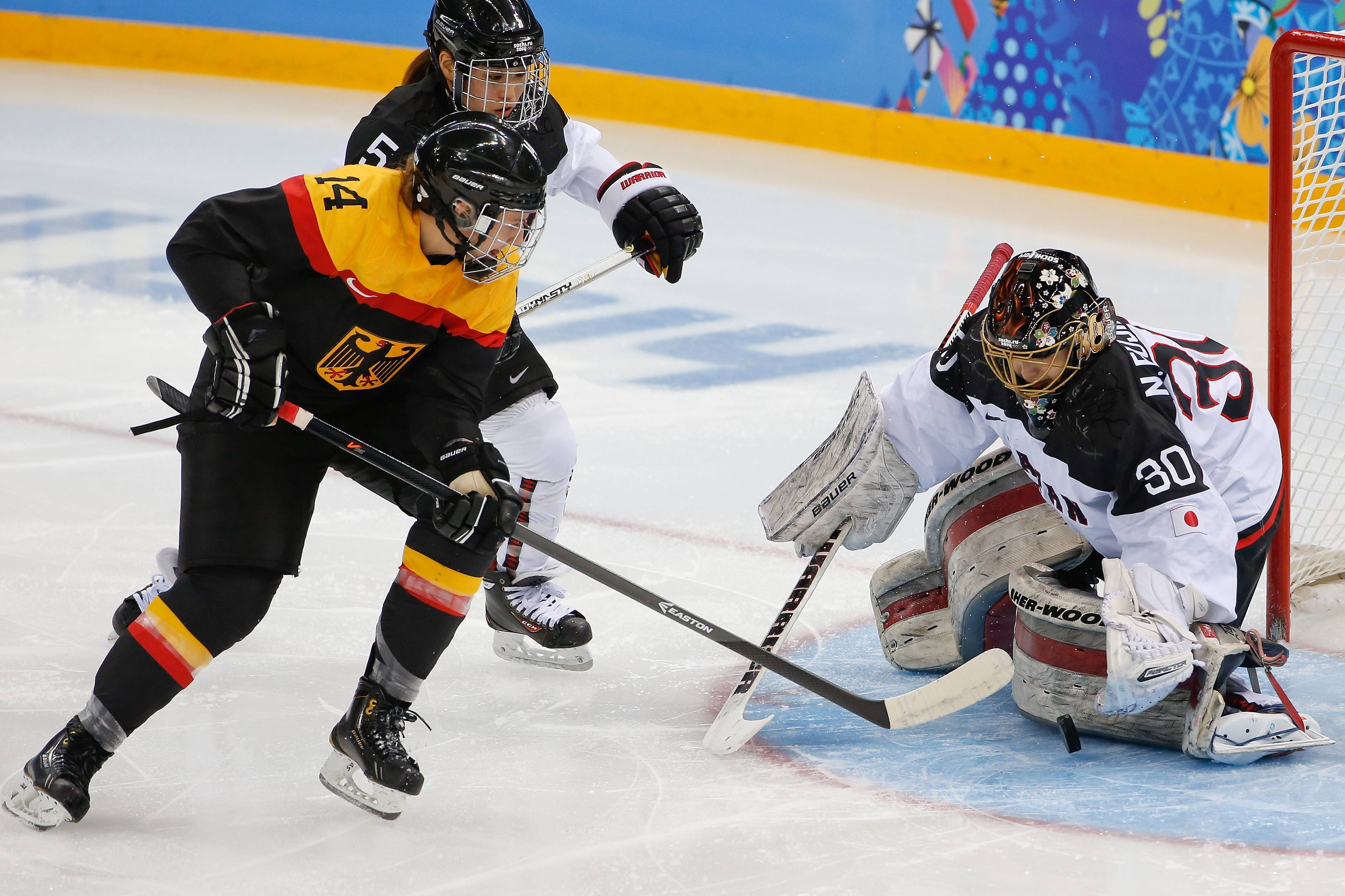 Goalkeeper Nana Fujimoto of Japan blocks Germany's Jacqueline Janzen shot Tuesday during the second period of the 2014 Winter Olympics women's ice hockey game at Shayba Arena in Sochi, Russia.
