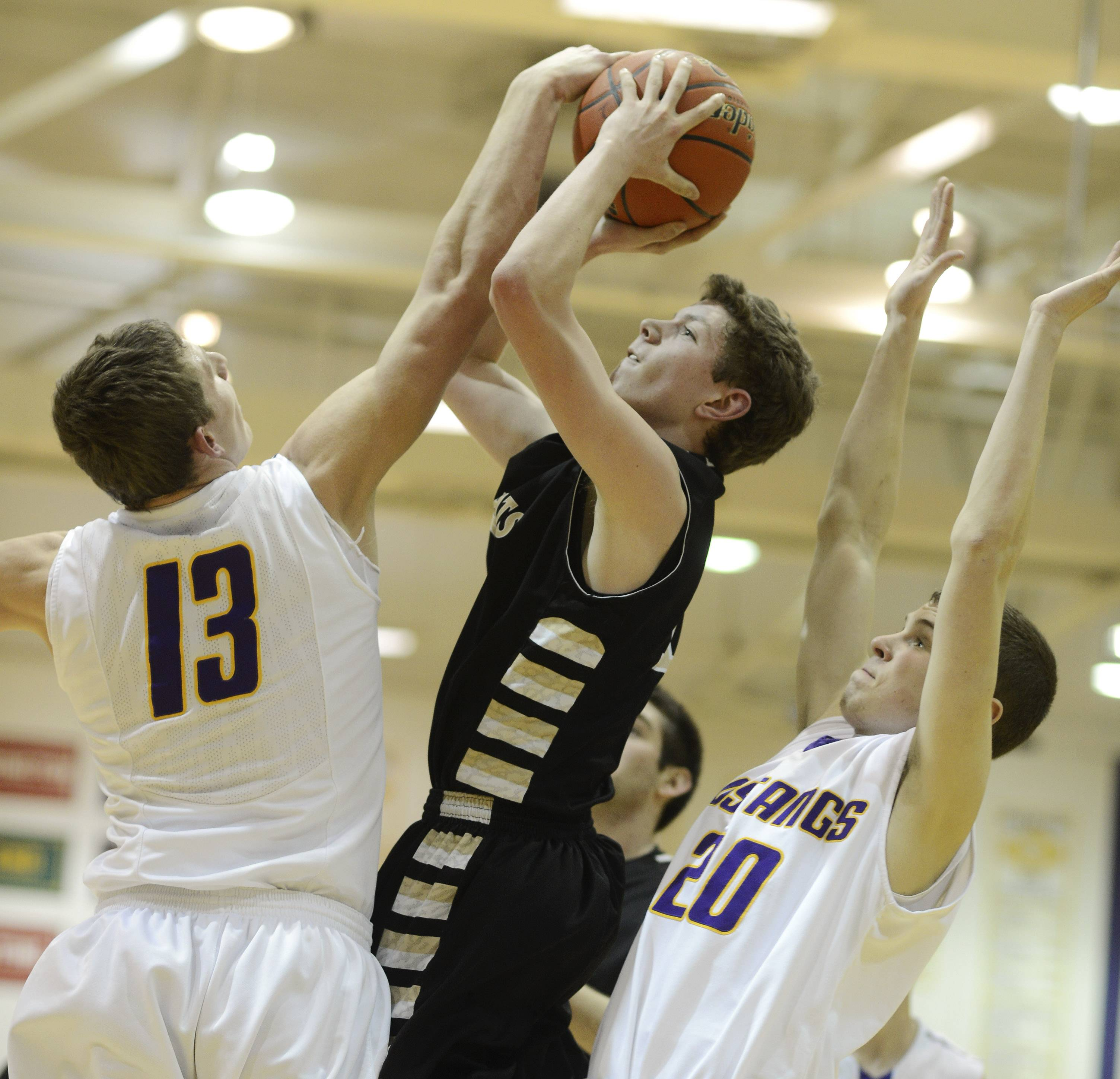 Graylake North's Lucas Buckels attempts a shot against Rolling Meadows' Matt Dolan, left, and Charlie Metzger during Tuesday's game at Rolling Meadows.