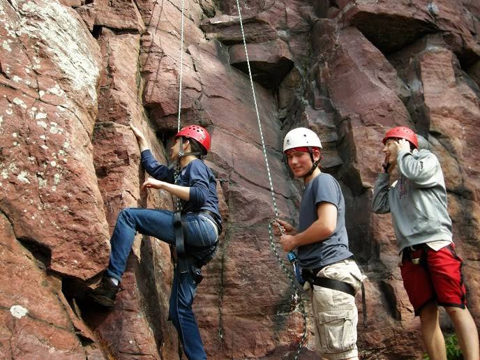 Boy Scouts, from left, Anthony Sorgani, Kyle Legge and Brian Bailey rock climb at Devil's Lake State Park in Wisconsin. Troop 140 provides its members with opportunities to travel and experience the outdoors.