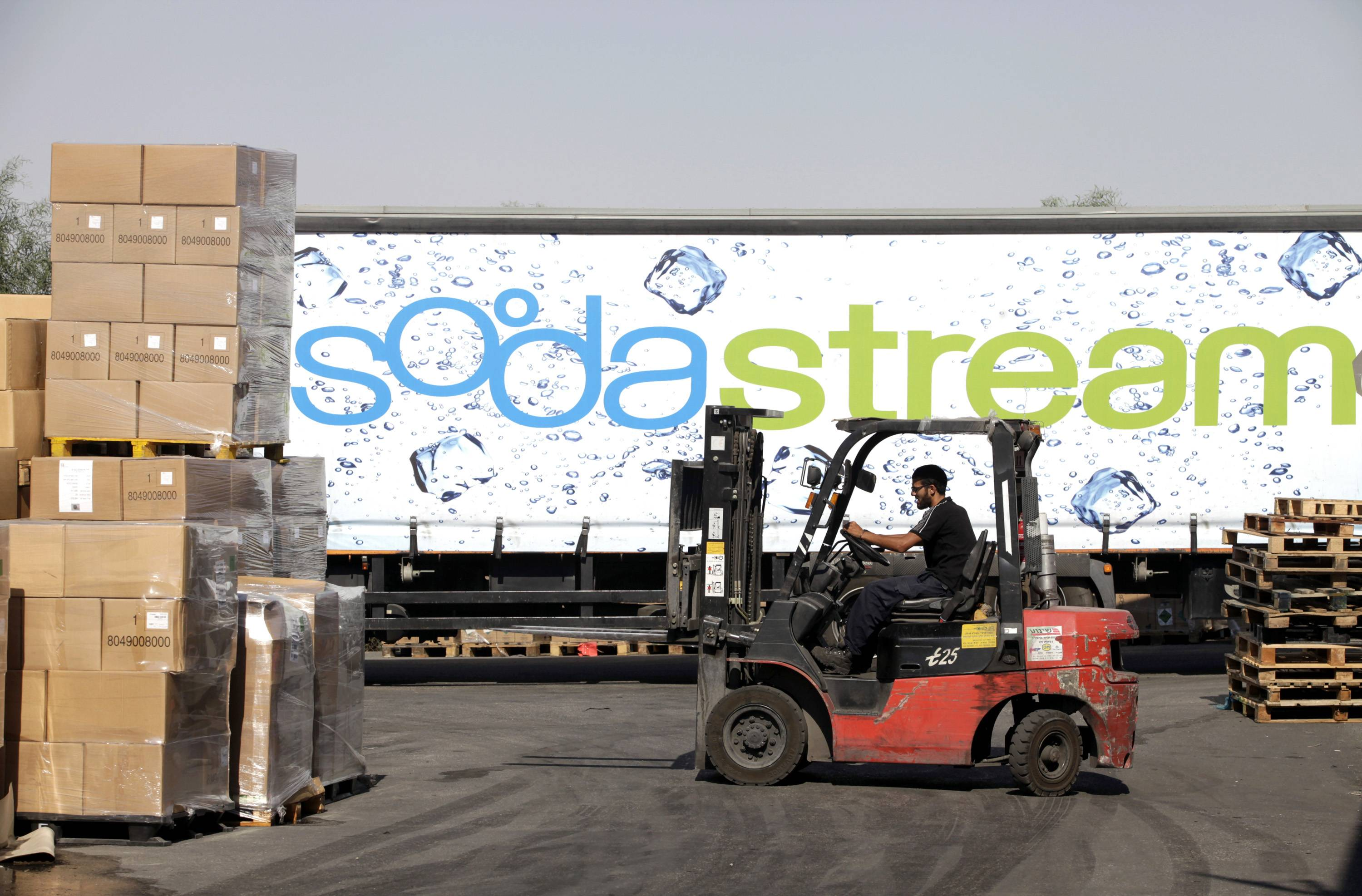 An employee uses a forklift truck to prepare pallets of SodaStream products for export at the SodaStream International Ltd. factory in Mishor Adumim, near Jerusalem, IsraelWednesday.