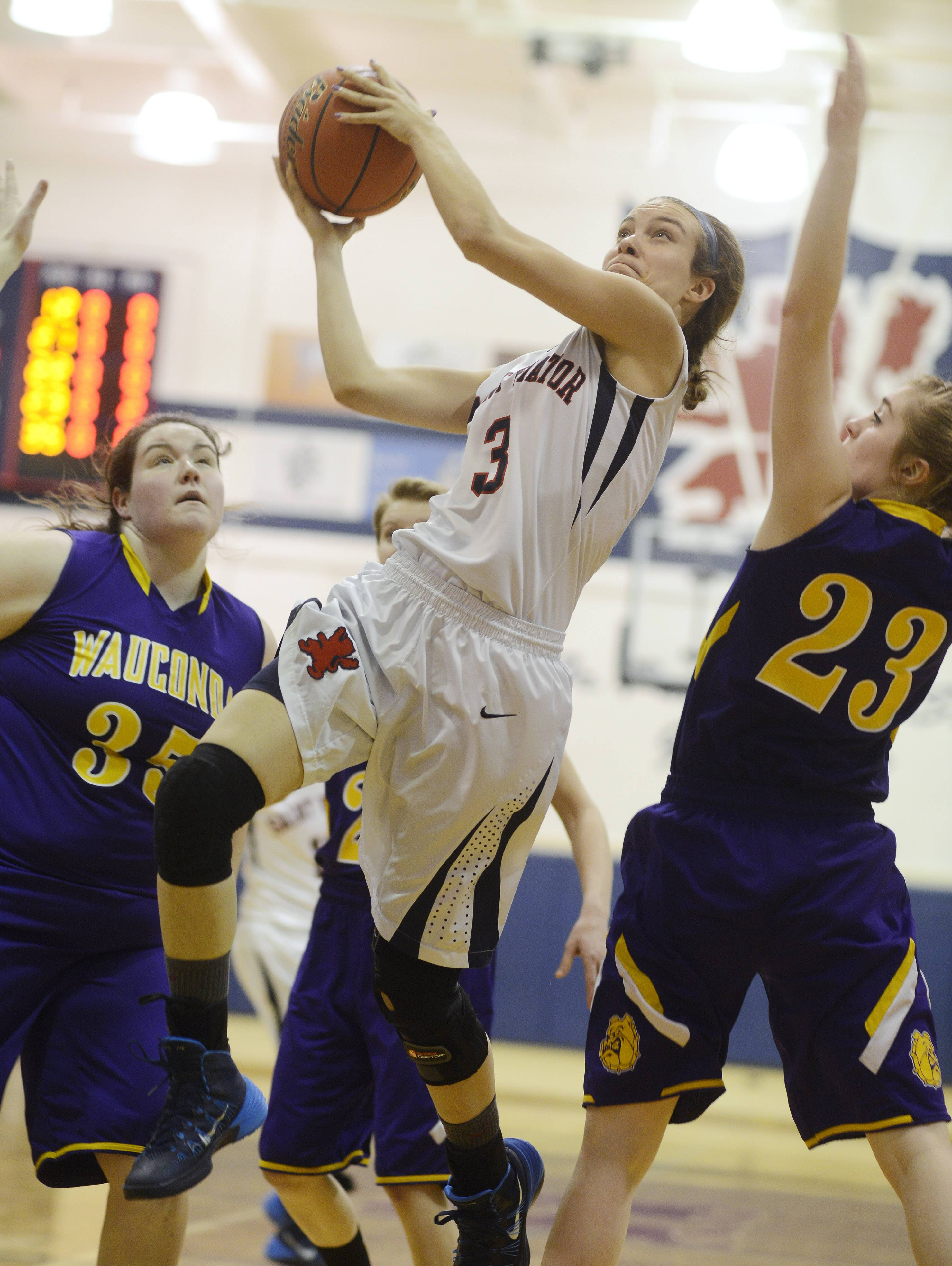 St. Viator's Kelsey Trimble, middle, drives to the basket against Wauconda defenders Dani Sturm, left, and Jessie Wood during Wednesday's game in Arlington Heights.