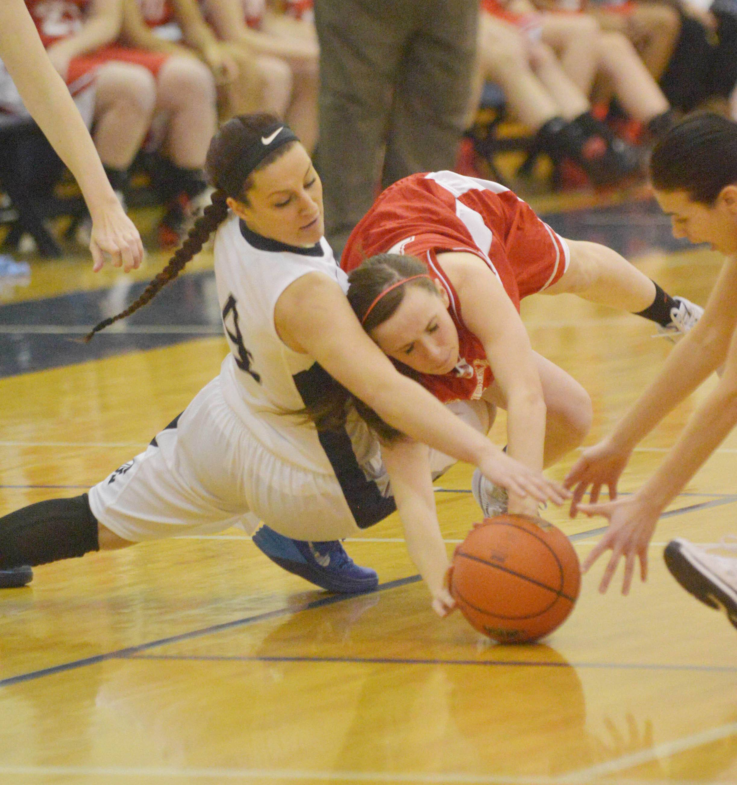 Julianna Wadsworth of Oswego East and Emily Kraft of Naperville Central dive for the ball.